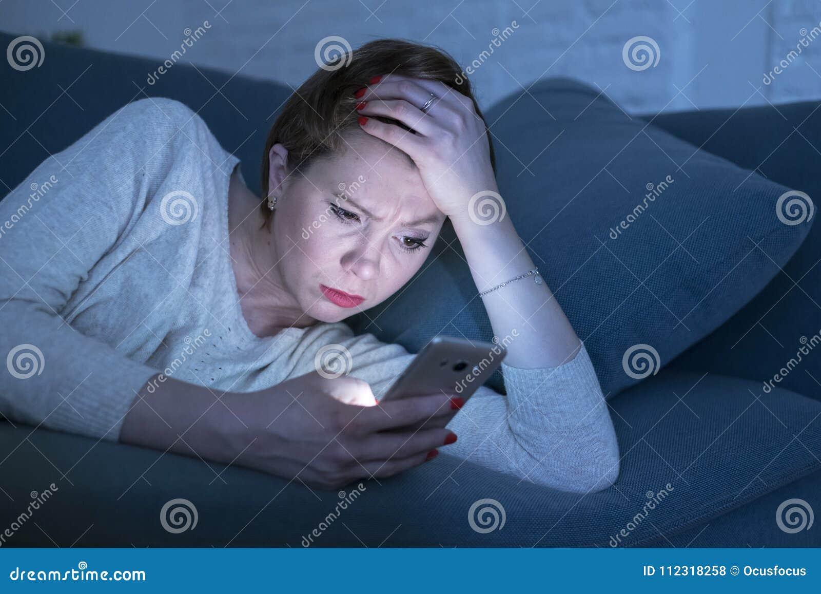 Retrato da jovem mulher 30s que encontra-se no sofá da cama tarde na noite em casa que usa os meios sociais app no telefone celul