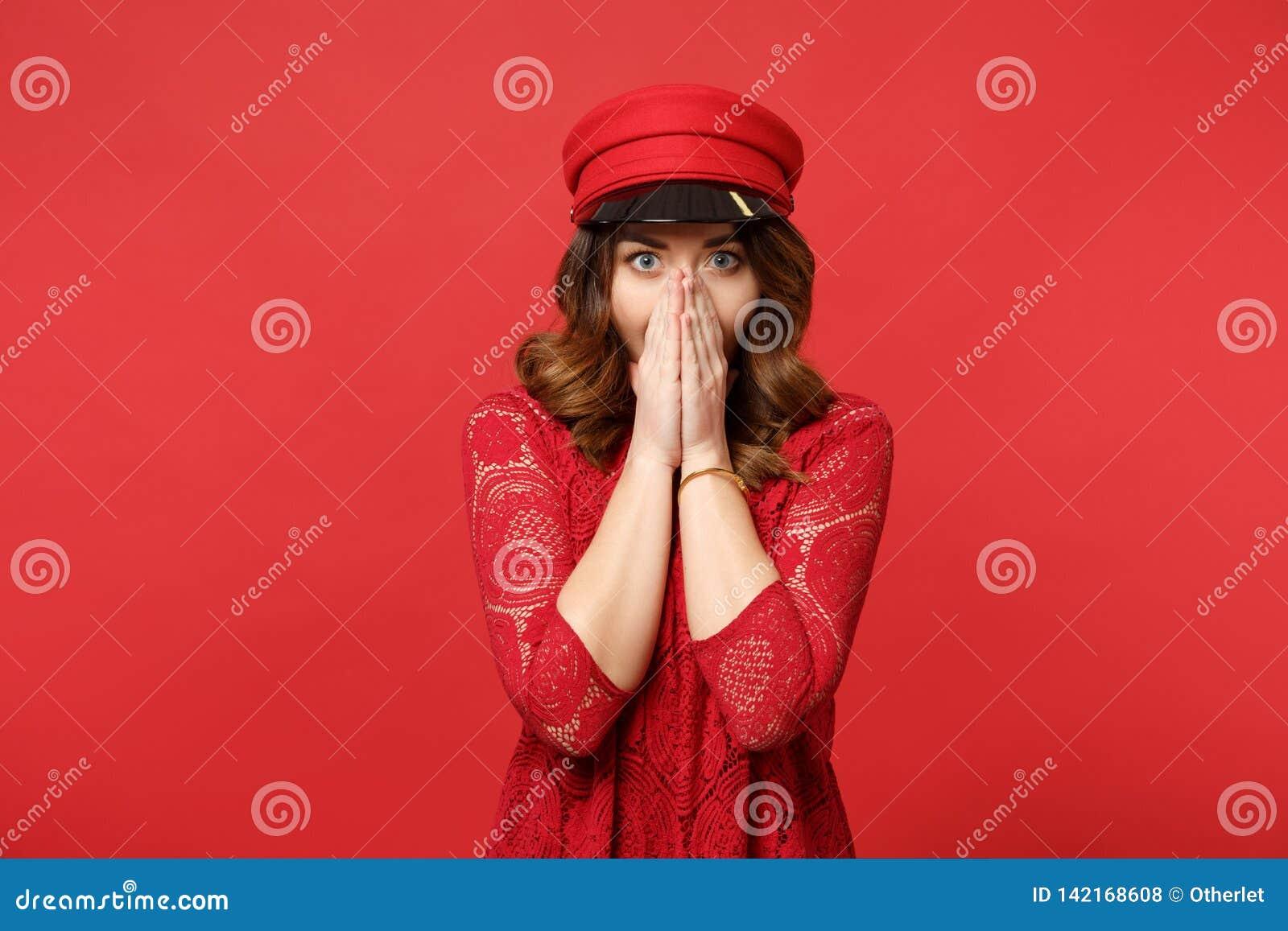 Retrato da jovem mulher surpreendida chocada na boca da coberta do vestido e do tampão do laço com as palmas isoladas na parede v