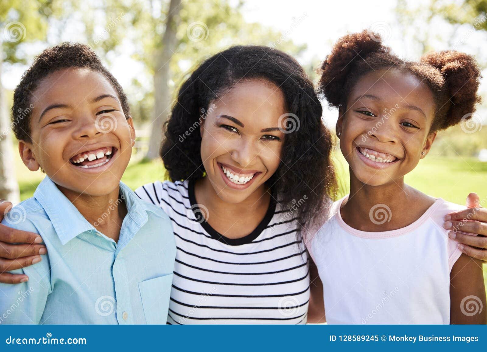 Retrato da mãe de sorriso com as crianças que relaxam no parque