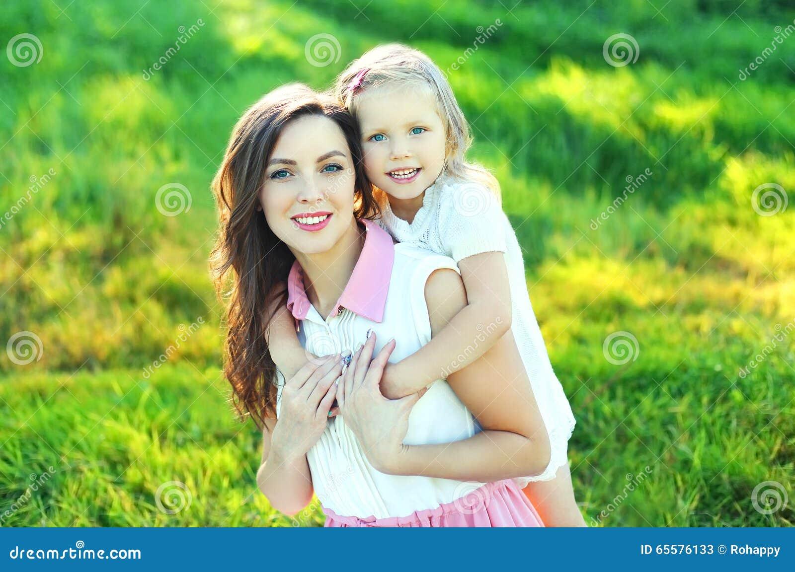 Retrato da mãe e da criança felizes junto no verão