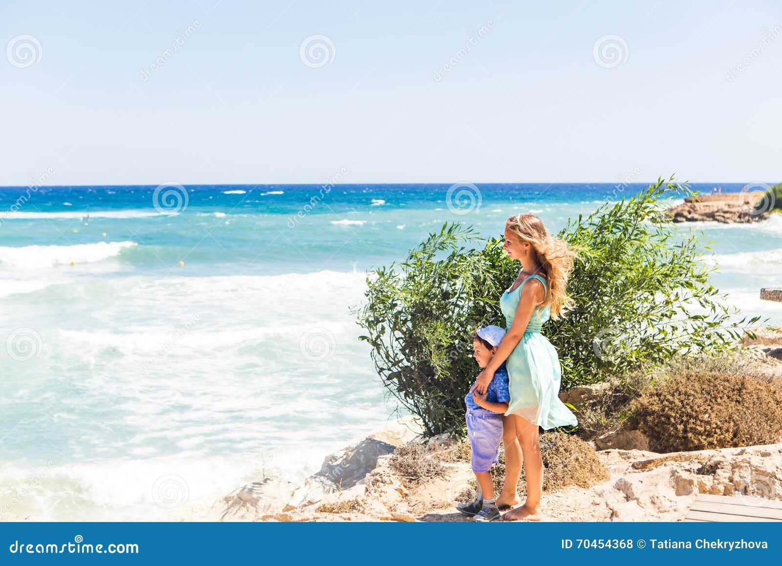 Retrato da mãe e do filho felizes no mar, exterior
