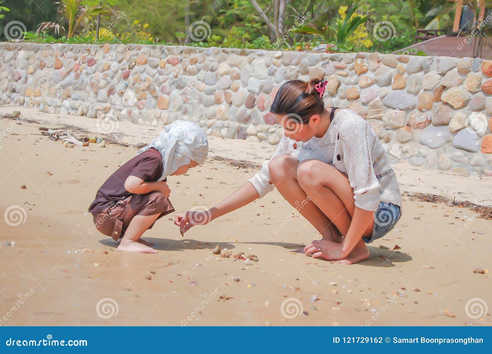 Retrato da mãe e do filho que jogam com a areia pelo mar