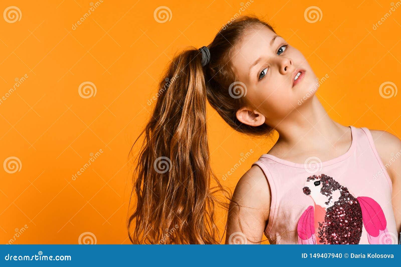 Retrato da menina ? moda bonita pequena da crian?a nas cal?as de brim