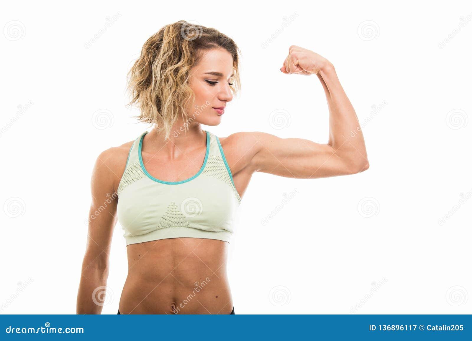 Retrato da menina apta que mostra seu bíceps