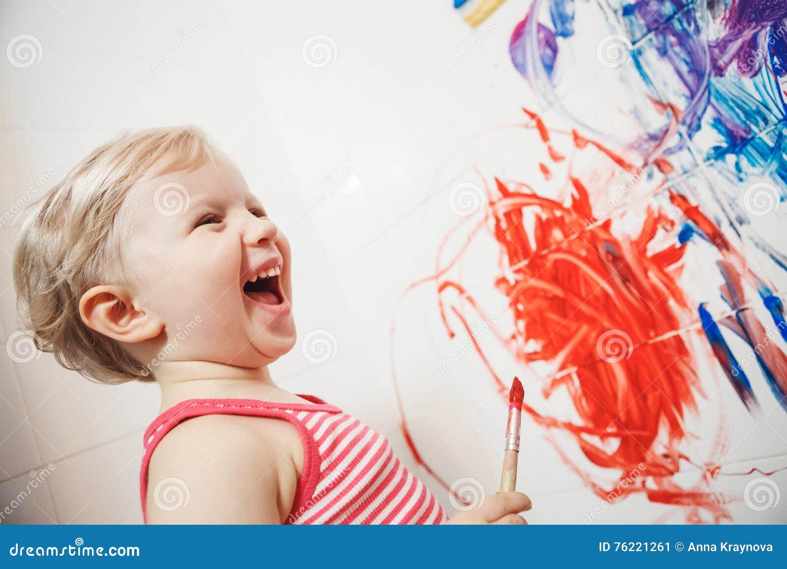Retrato da menina caucasiano branca adorável bonito do rapaz pequeno que joga e que pinta com pinturas na parede no banheiro