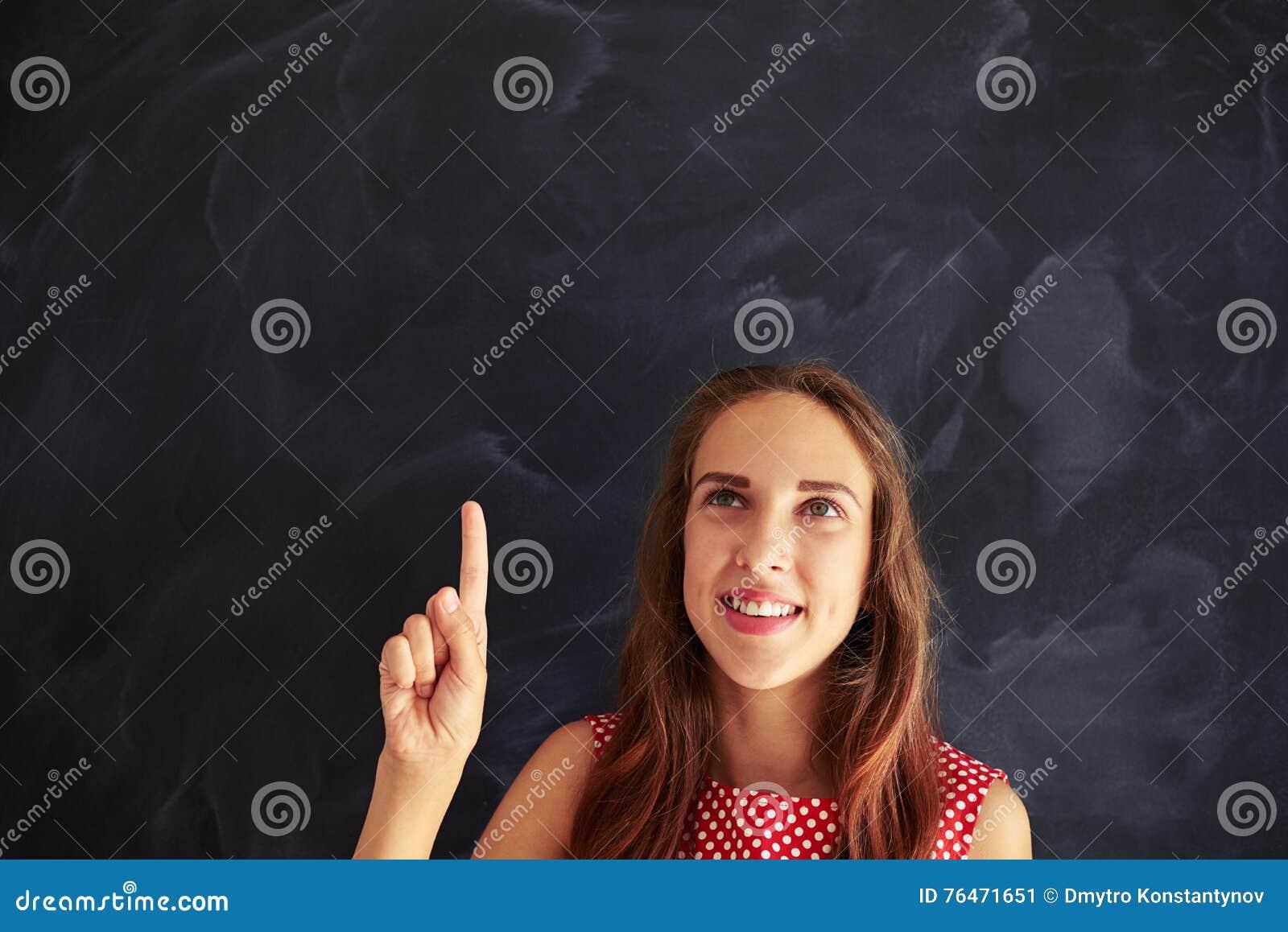 Retrato da menina de sorriso com o dedo indicador aguçado que olha acima o agai