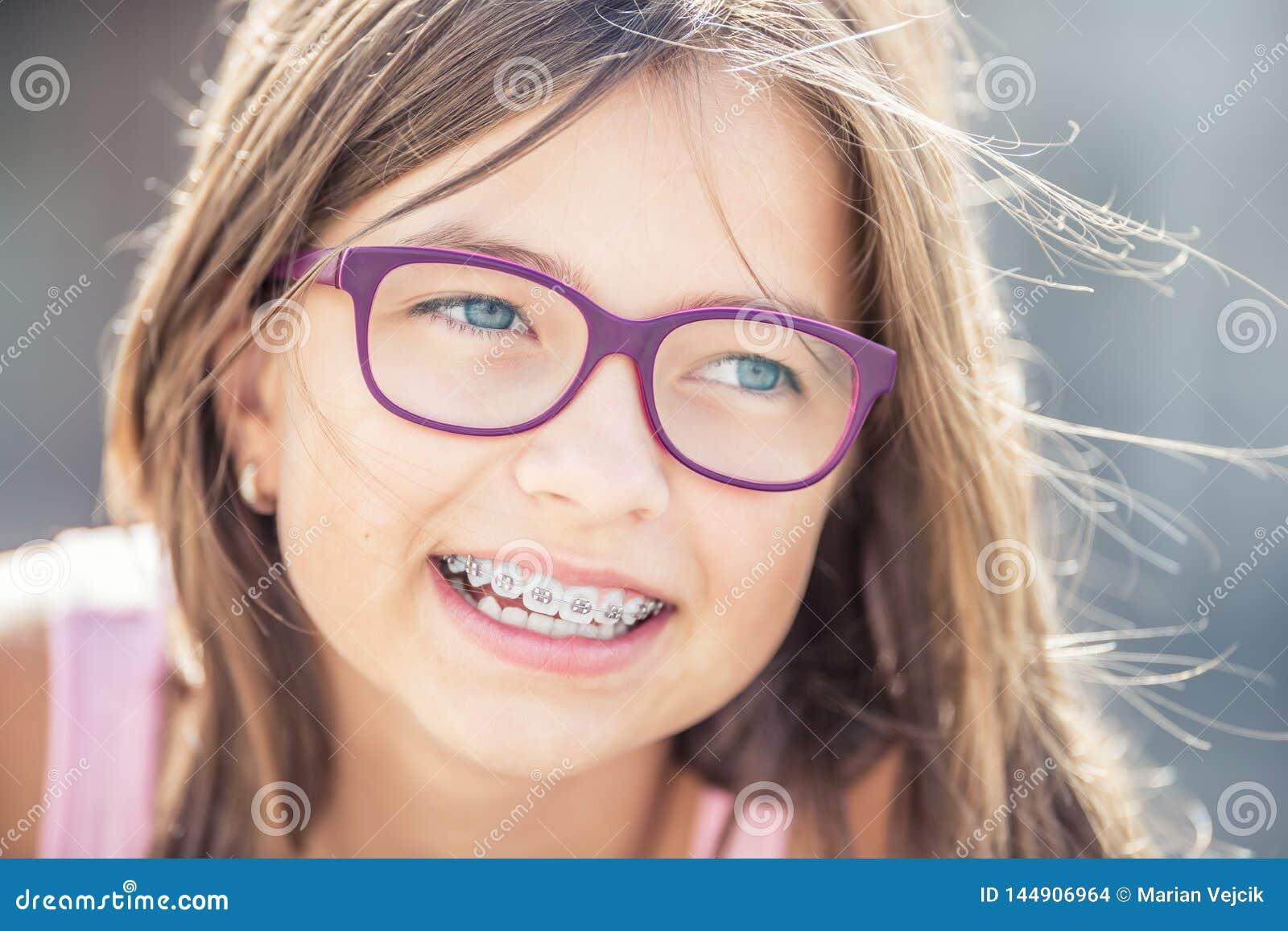 Retrato da menina de sorriso feliz com cintas e vidros dentais