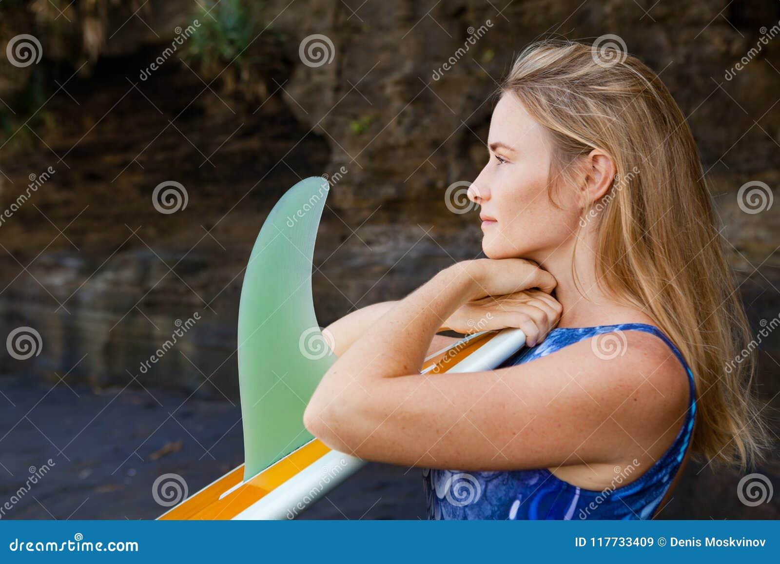 Retrato da menina do surfista com a prancha no fundo do penhasco do mar