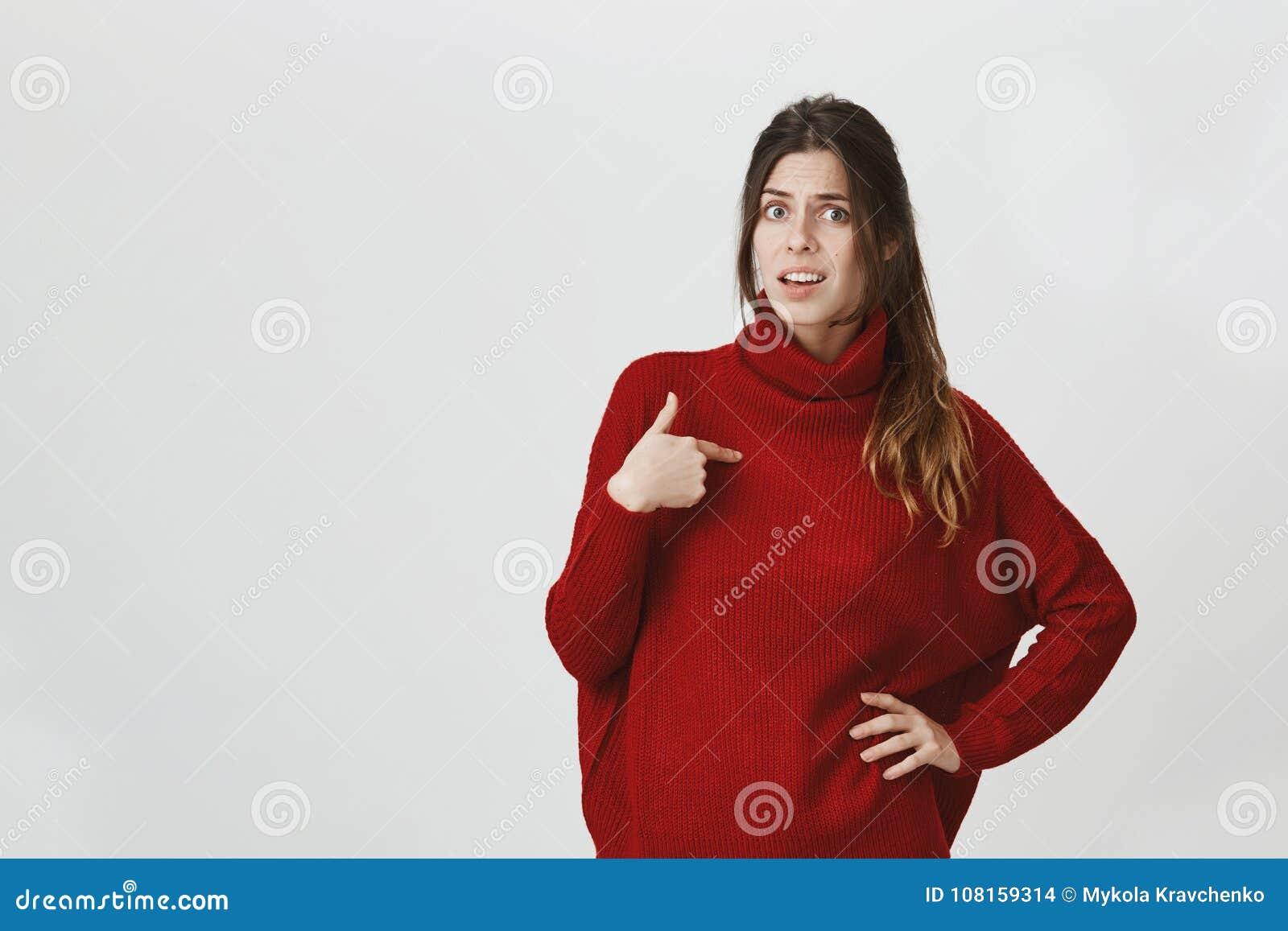 Retrato da menina europeia bonita nova que olha ser acusado confundido em algo, apontando nsi mesma que veste
