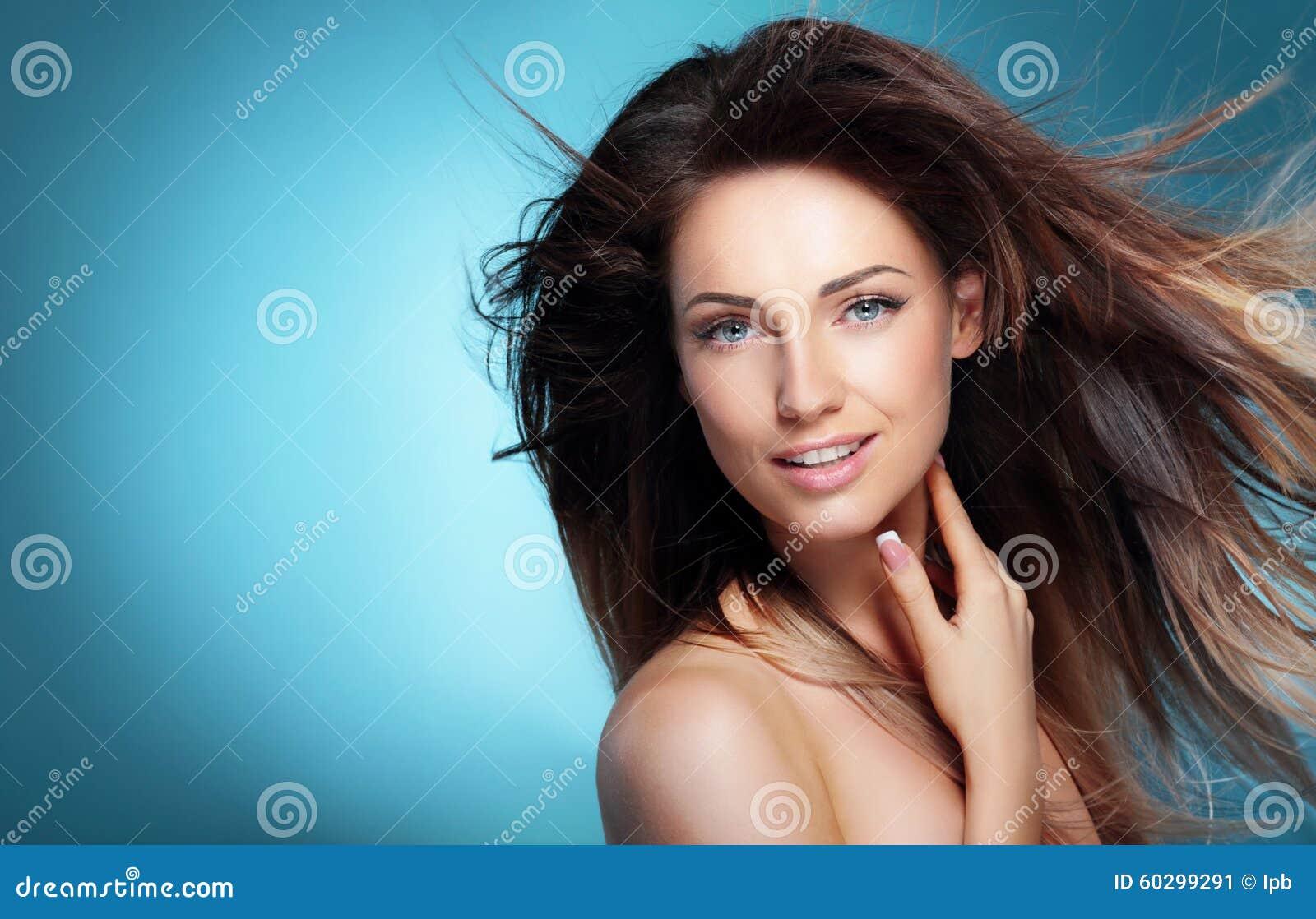 Retrato da menina feliz com cabelo de sopro escuro longo contra o azul