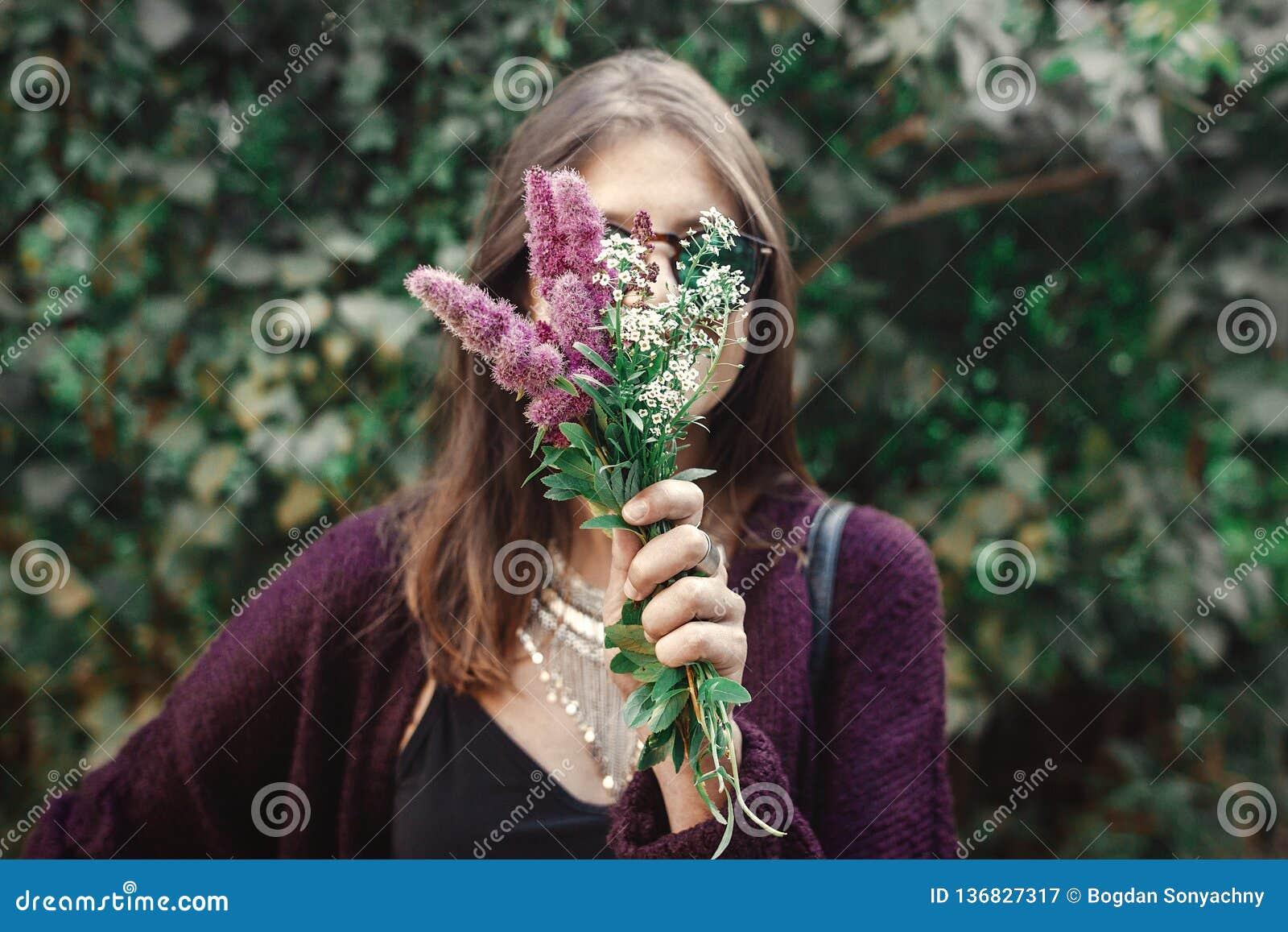 Retrato da menina feliz do boho nos óculos de sol que sorri com o ramalhete dos wildflowers no jardim ensolarado Menina despreocu