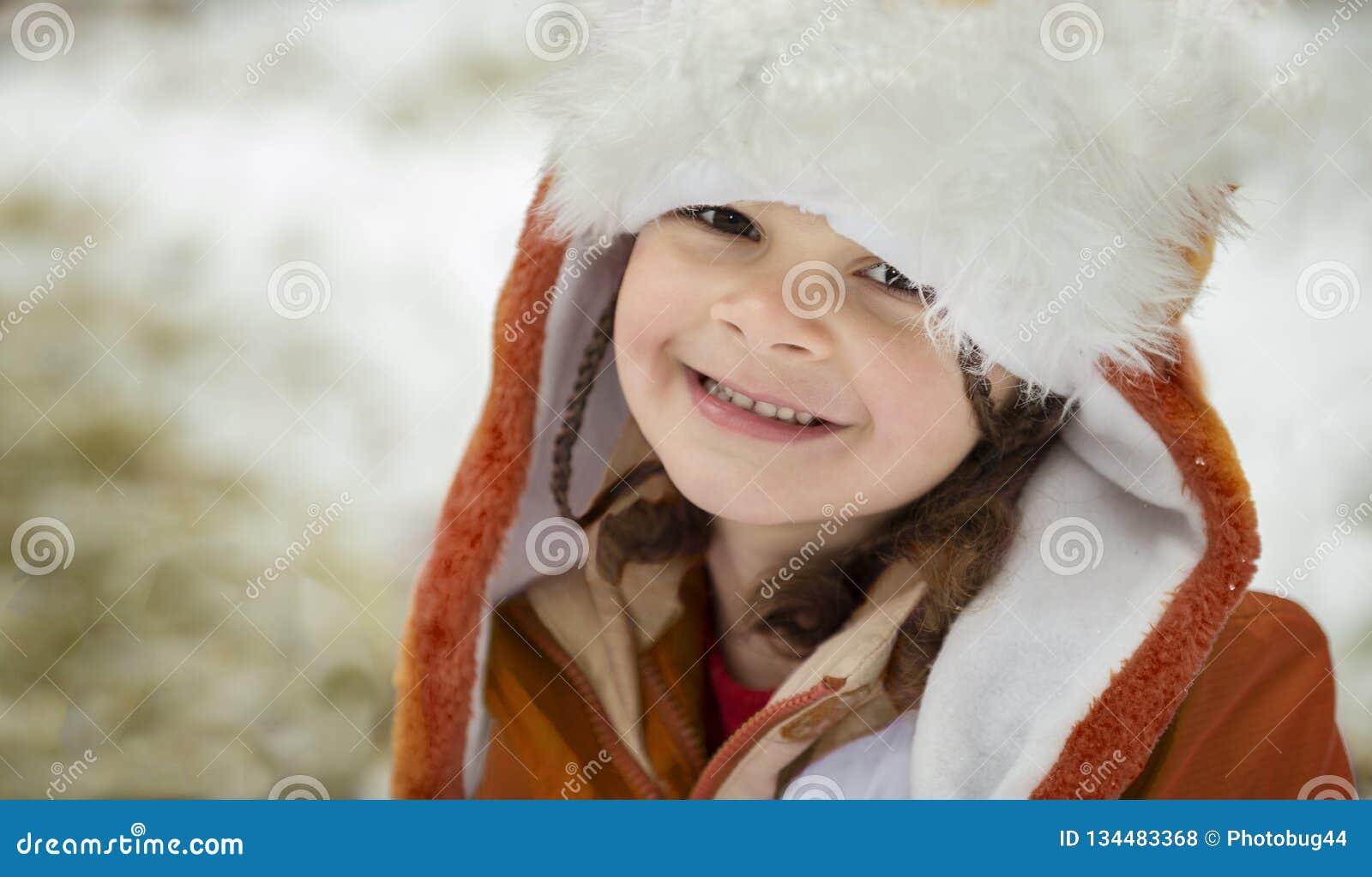 Retrato da menina no chapéu e no revestimento do inverno