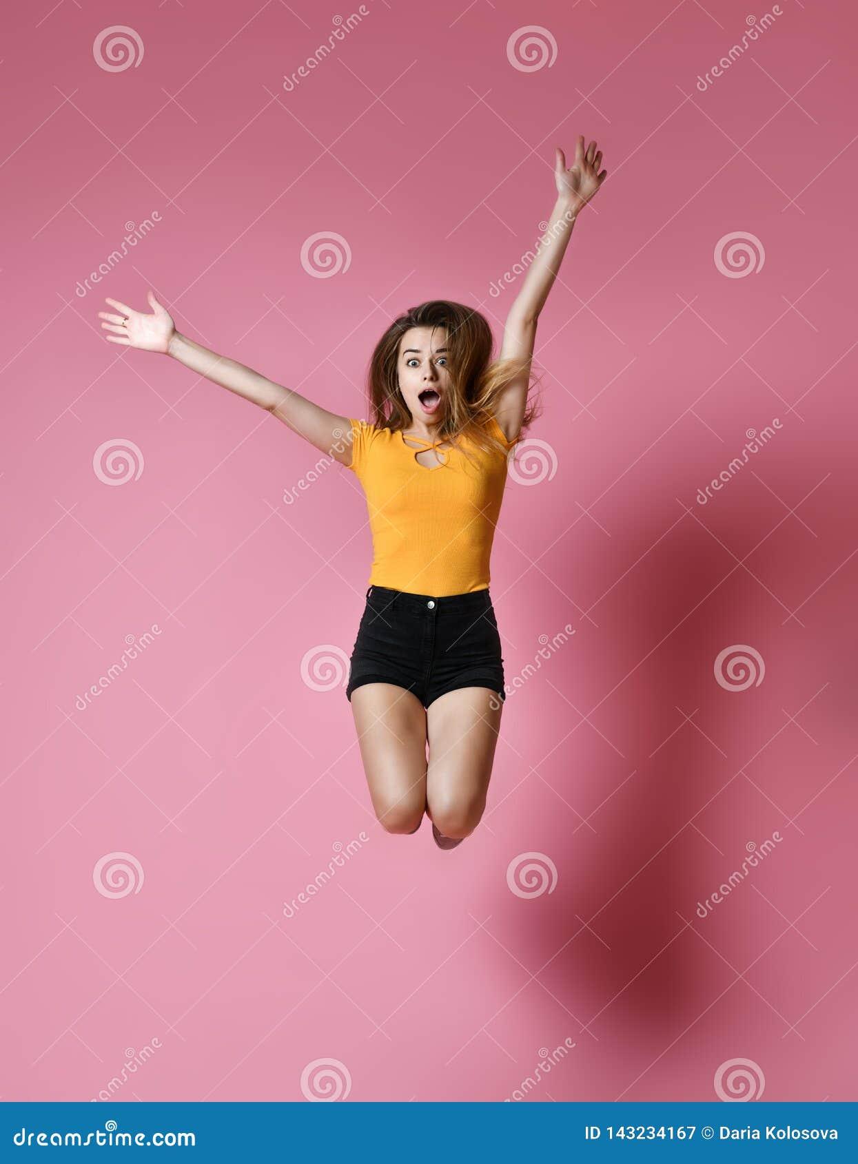 Retrato da menina positiva alegre que salta no ar que olha a câmera isolada no fundo cor-de-rosa