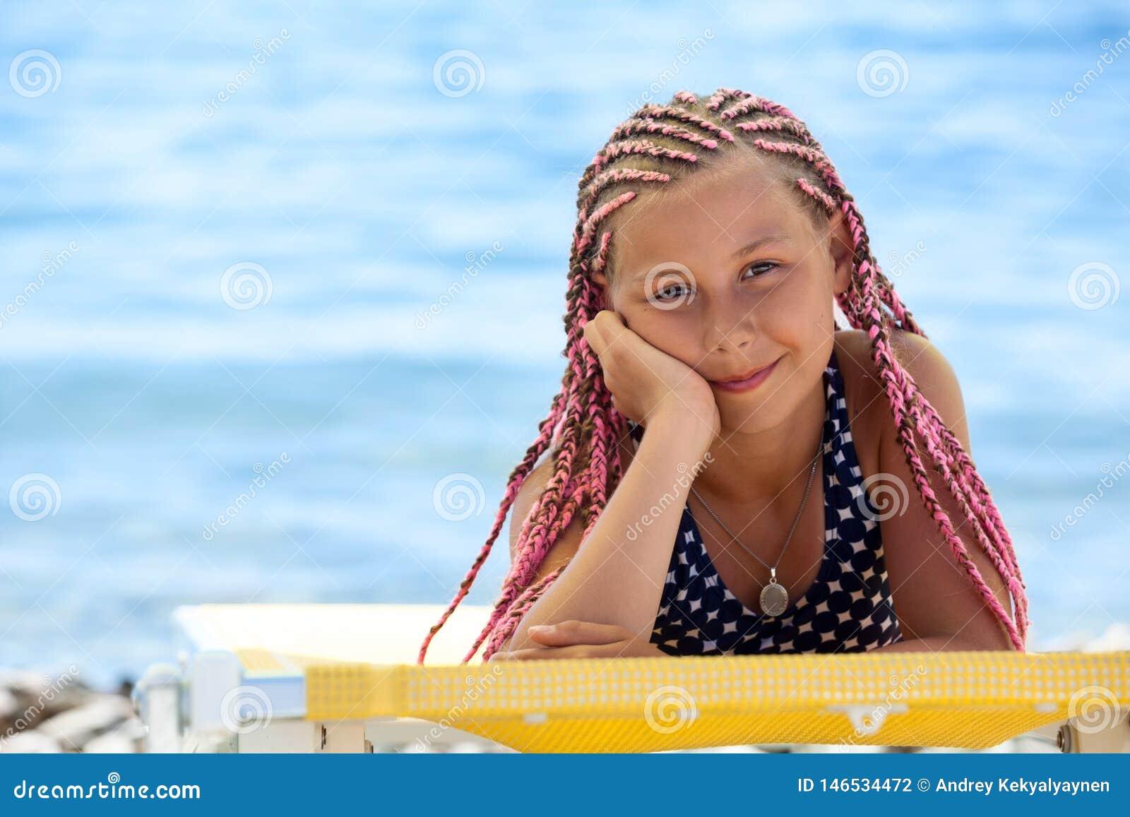 Retrato da menina preteen com penteado cor-de-rosa dos dreadlocks que bronzea-se na praia no seacoast