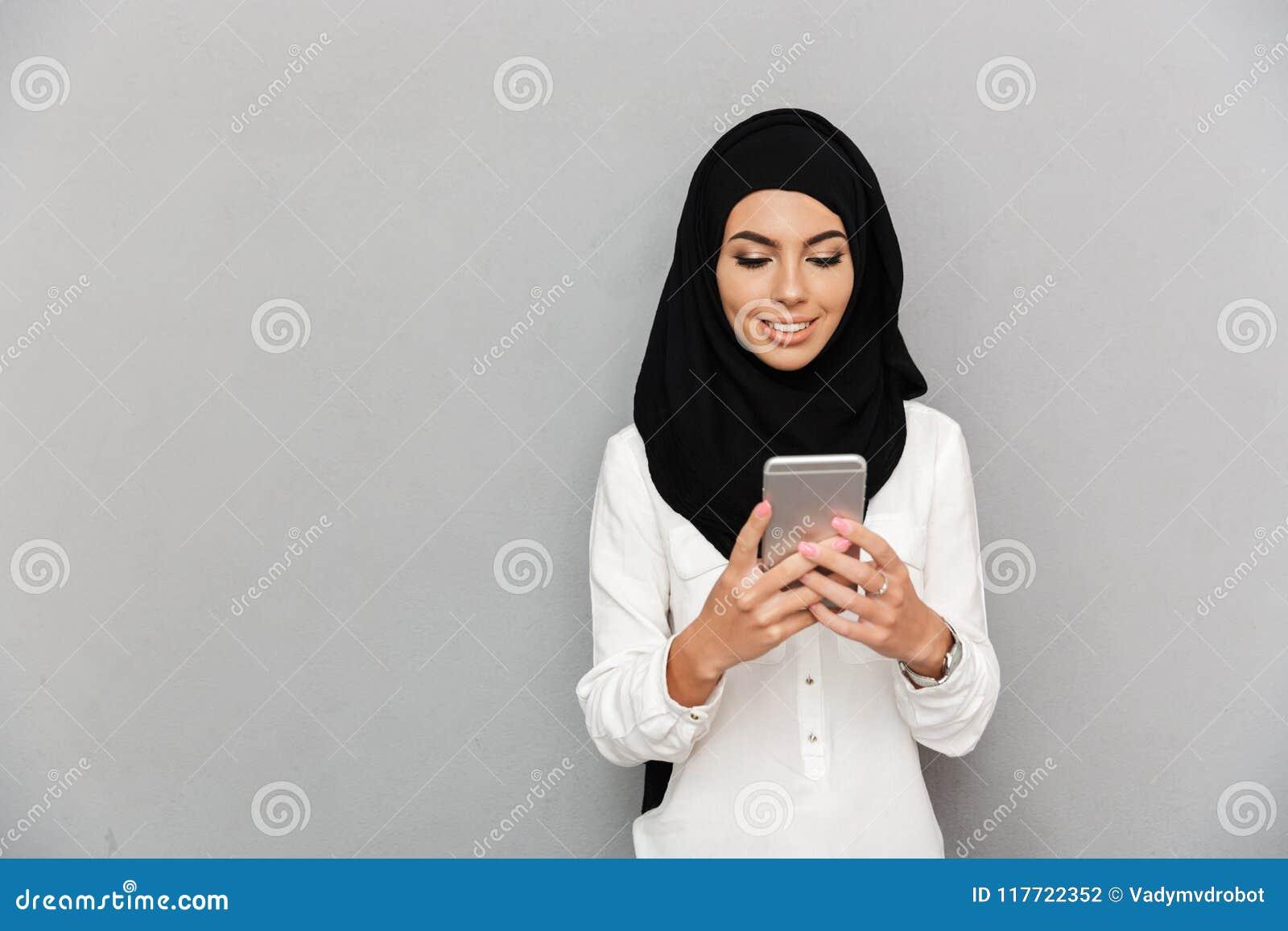 Retrato da mulher árabe bonita no sorriso e no usin do lenço