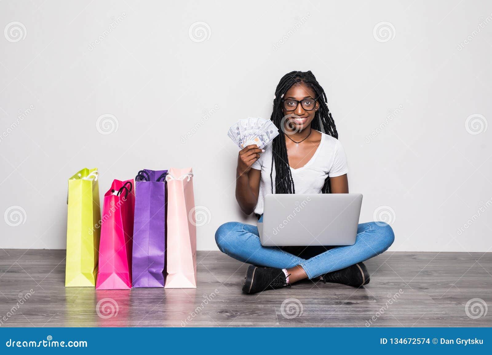 Retrato da mulher afro-americana nova que usa o portátil ao sentar-se em um assoalho com as cédulas dos dólares perto dos sacos d