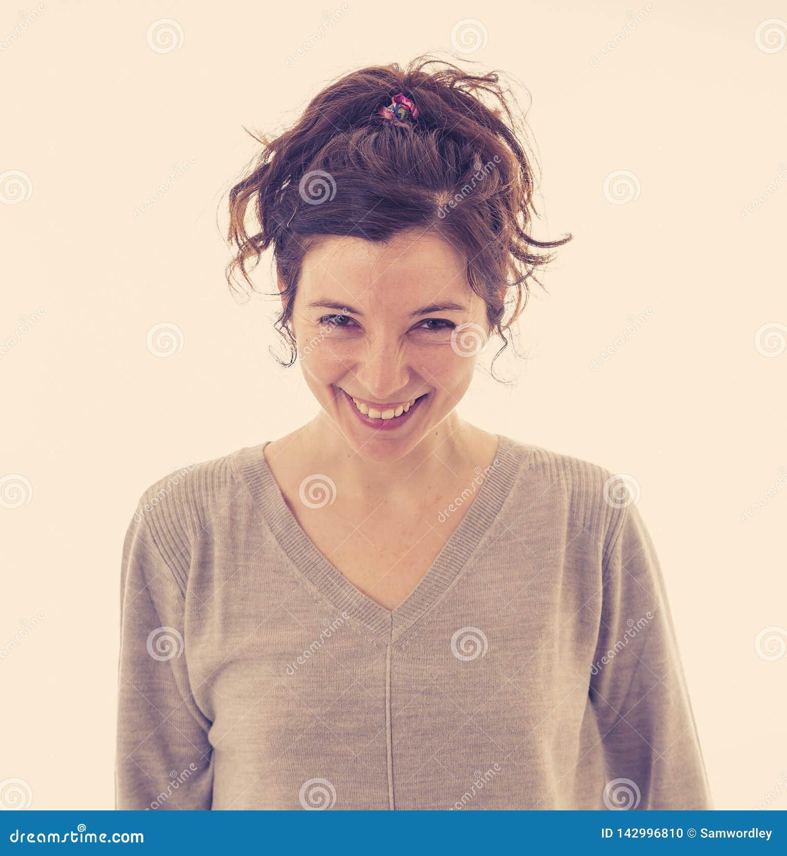 Retrato da mulher alegre atrativa nova com a cara feliz de sorriso Expressões e emoções humanas