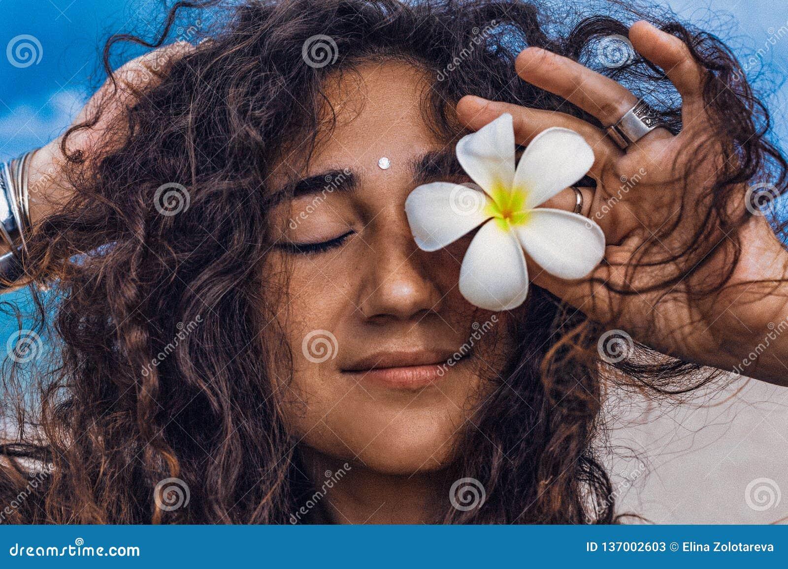 Retrato da mulher alegre nova e bonita com a flor do frangipani na praia