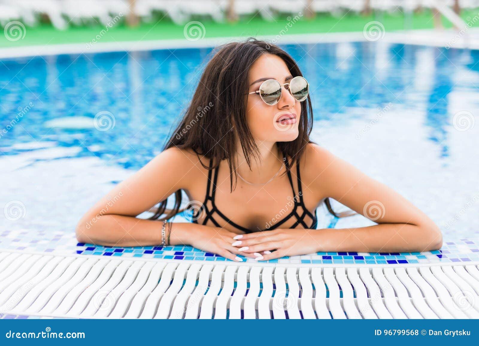 Retrato da mulher alegre  sexy  que relaxa na piscina luxuosa Menina na associação do spa resort do curso Férias de verão
