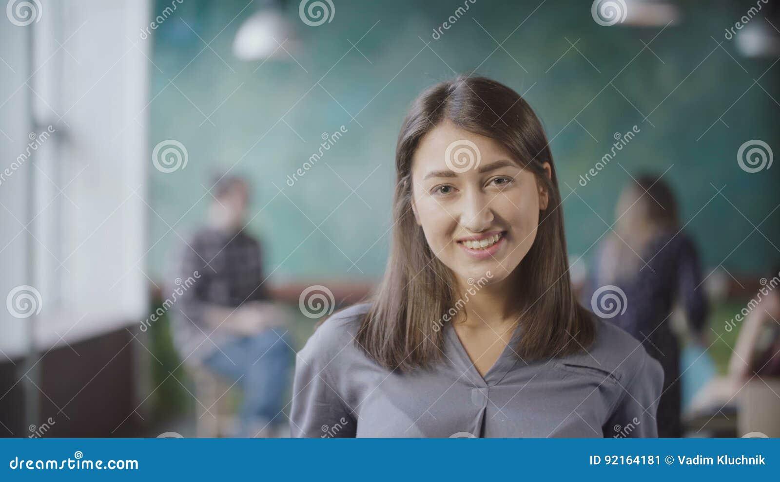 Retrato da mulher asiática bonita no escritório moderno Mulher de negócios bem sucedida nova que olha a câmera, sorrindo