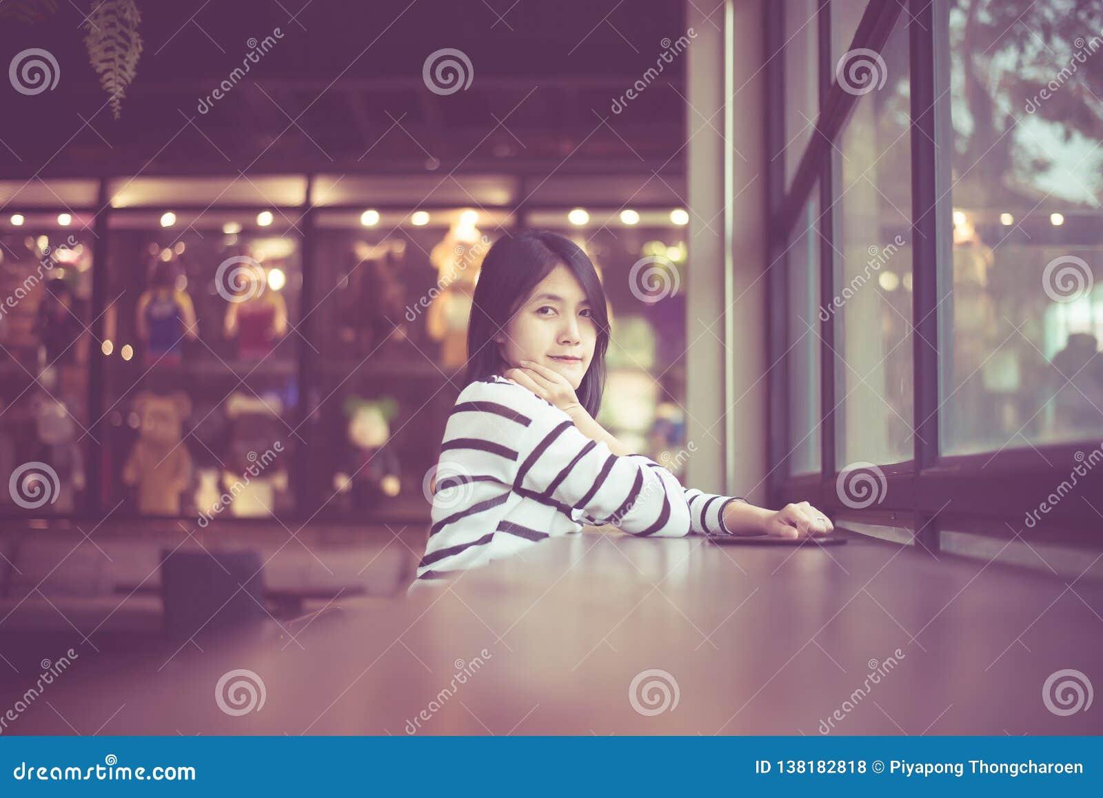 Retrato da mulher asiática bonita que sorri e que olha a câmera no café da cafetaria, feliz e fresco com pensamento positivo, vin