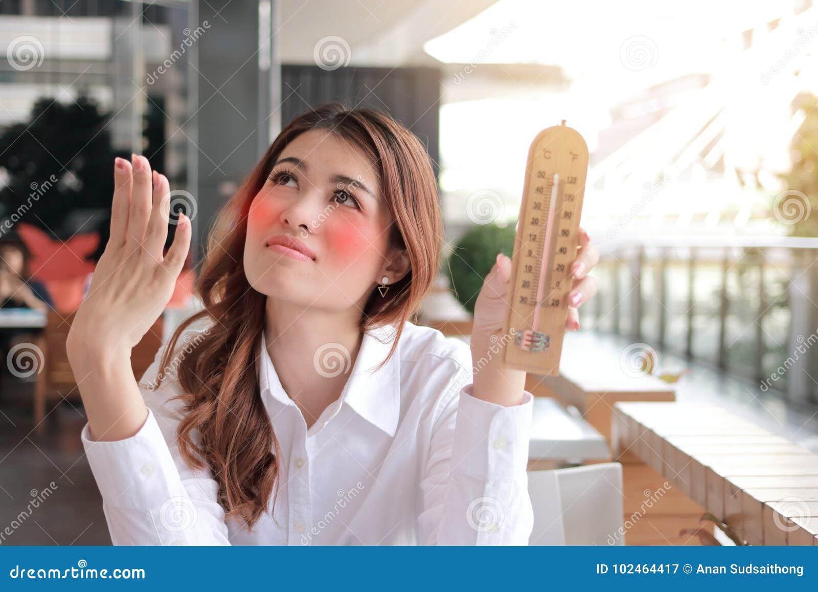 Retrato da mulher asiática nova que guarda o termômetro e que sente tão quente com alta temperatura na mesa contra o CCB do efeit