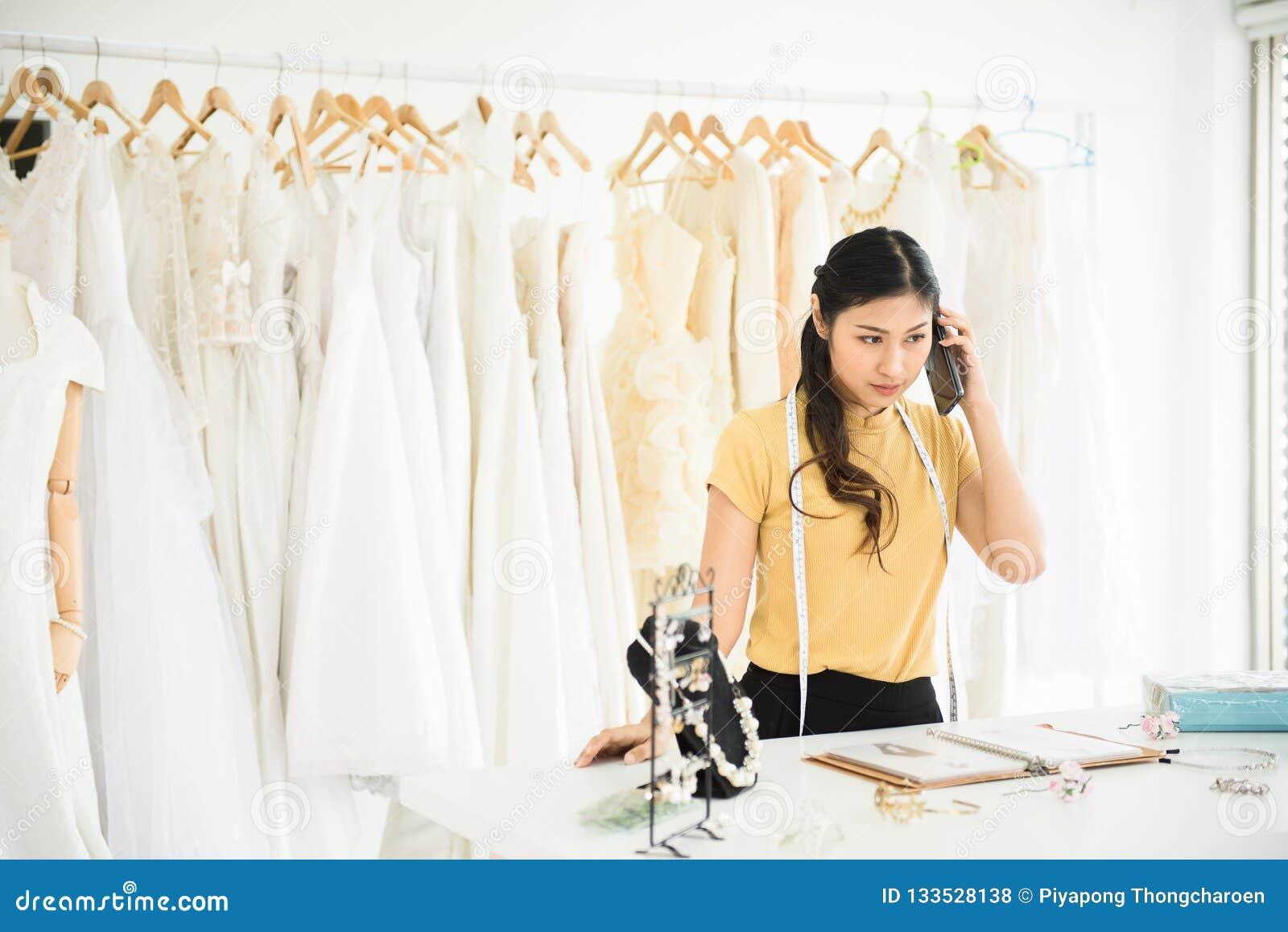Retrato da mulher asiática que trabalha e que usa o telefone celular na loja do vestido de casamento, a costureira bonita na loja