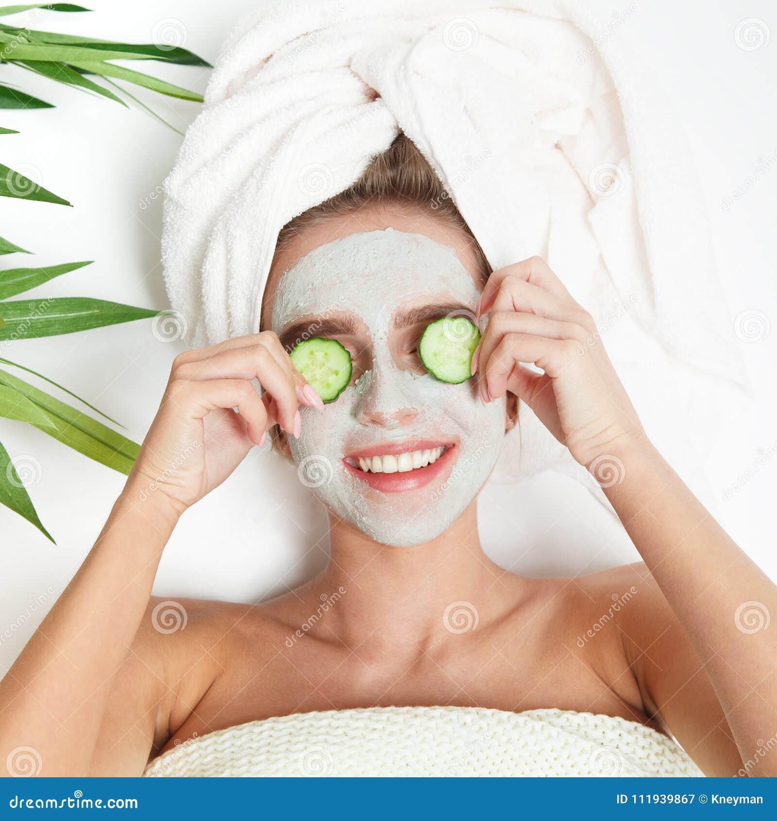 Retrato da mulher da beleza que coloca com a toalha na cabeça, pepino em seus olhos, máscara facial Terapia dos termas relaxe