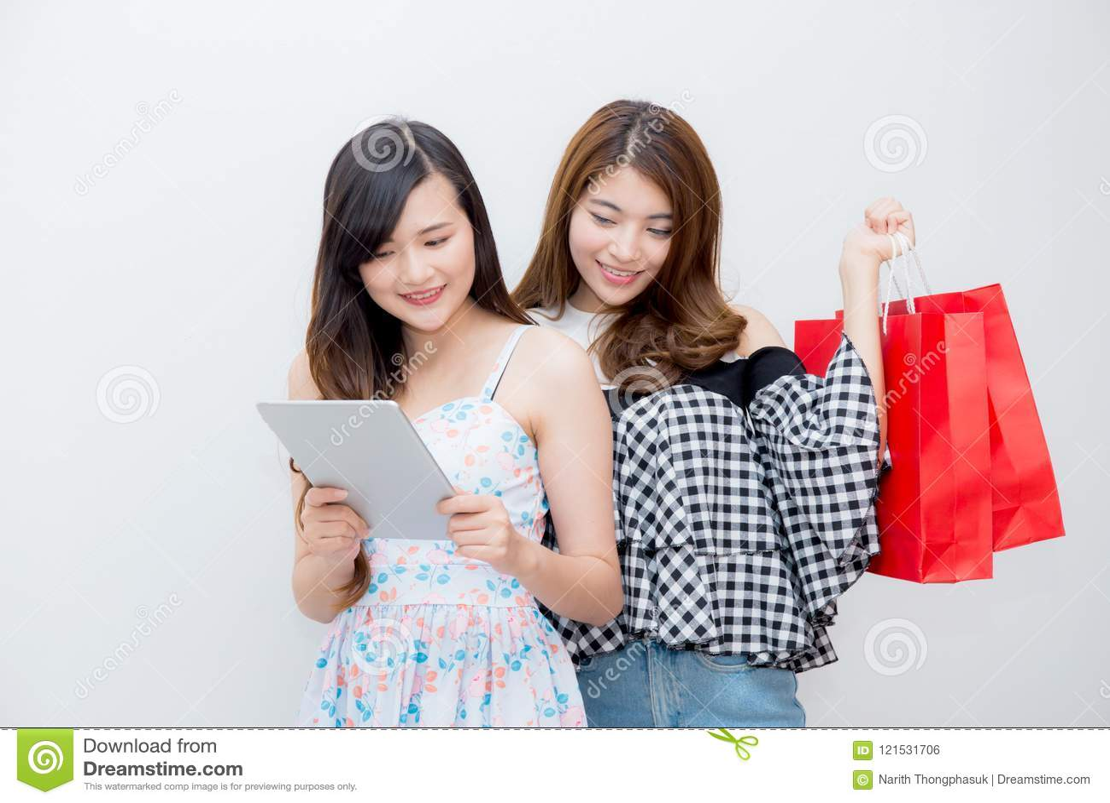 Retrato da mulher bonita asiática dos povos dos jovens dois que guarda o saco de compras e o tablet pc