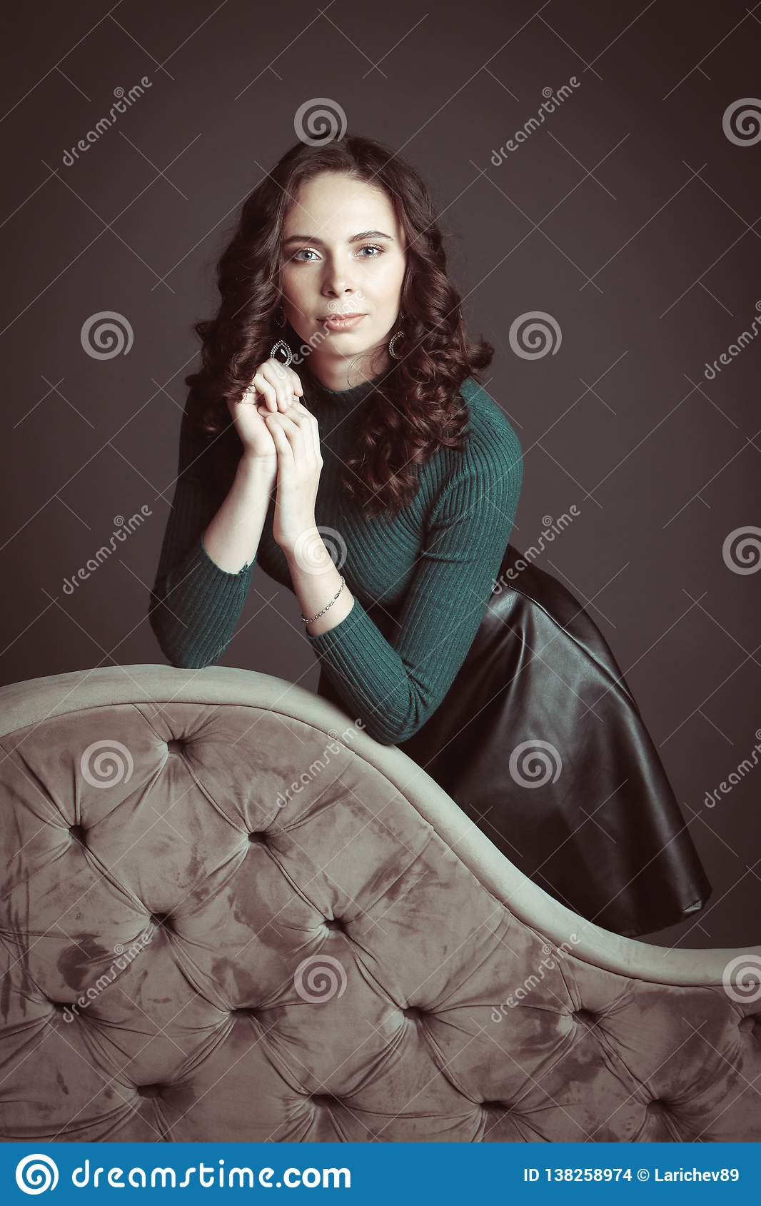 Retrato da mulher bonita com composição, em um sofá, na camiseta verde e na saia de couro preta que levantam no fundo escuro do c