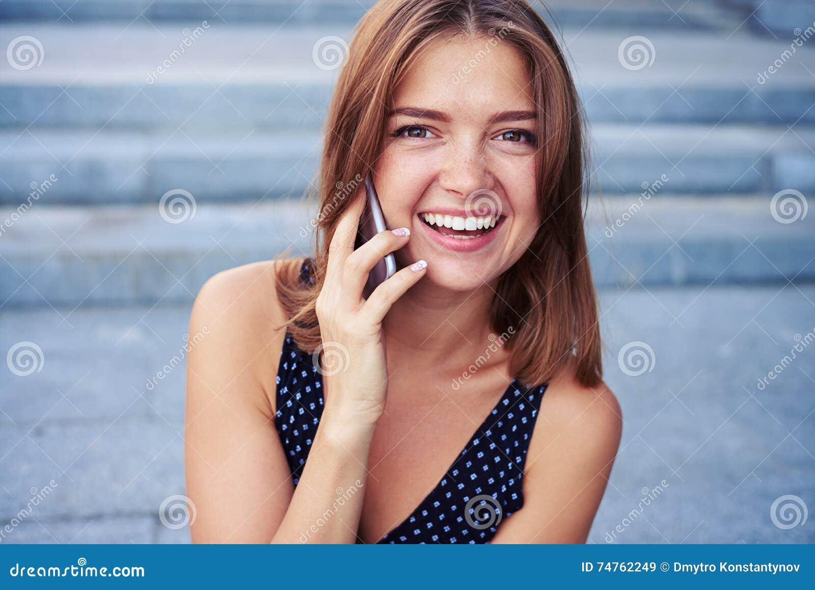 Retrato da mulher bonita de sorriso que fala no telefone com b