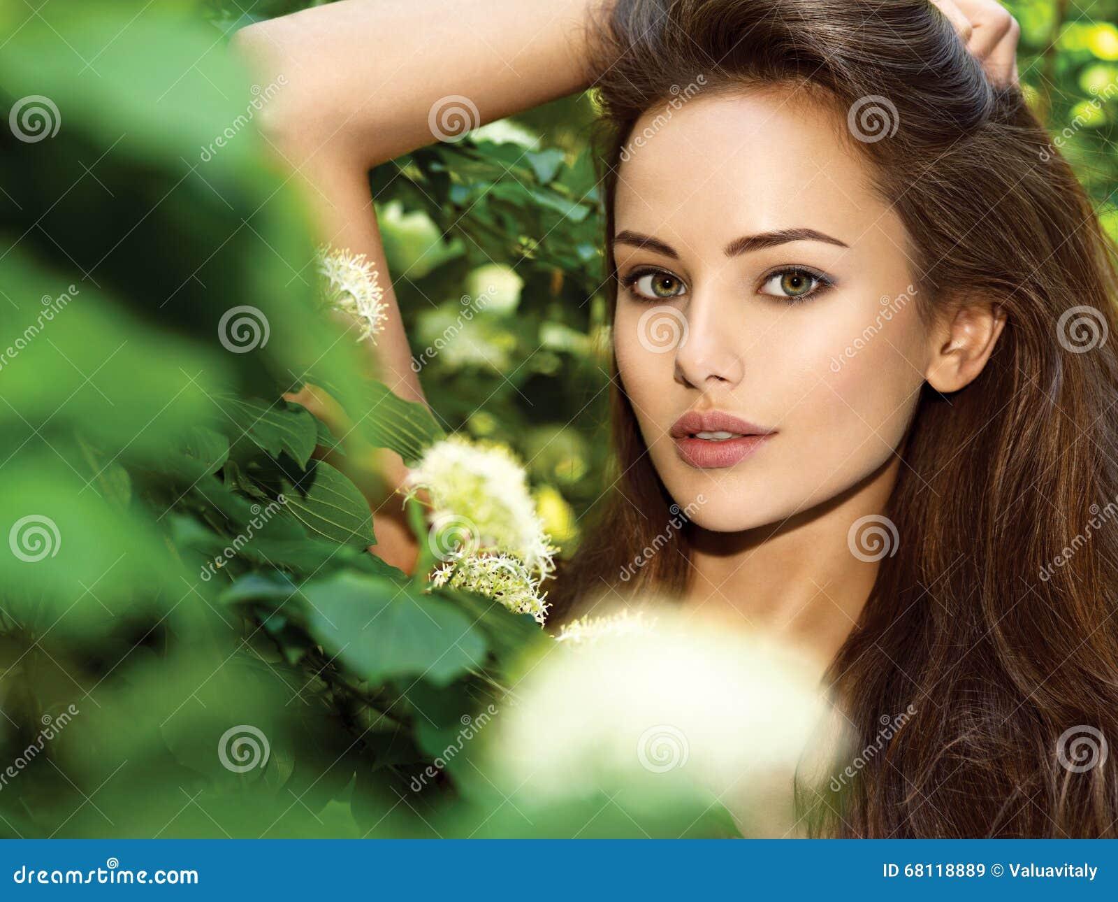 Retrato da mulher bonita nova com cabelos longos outdoors