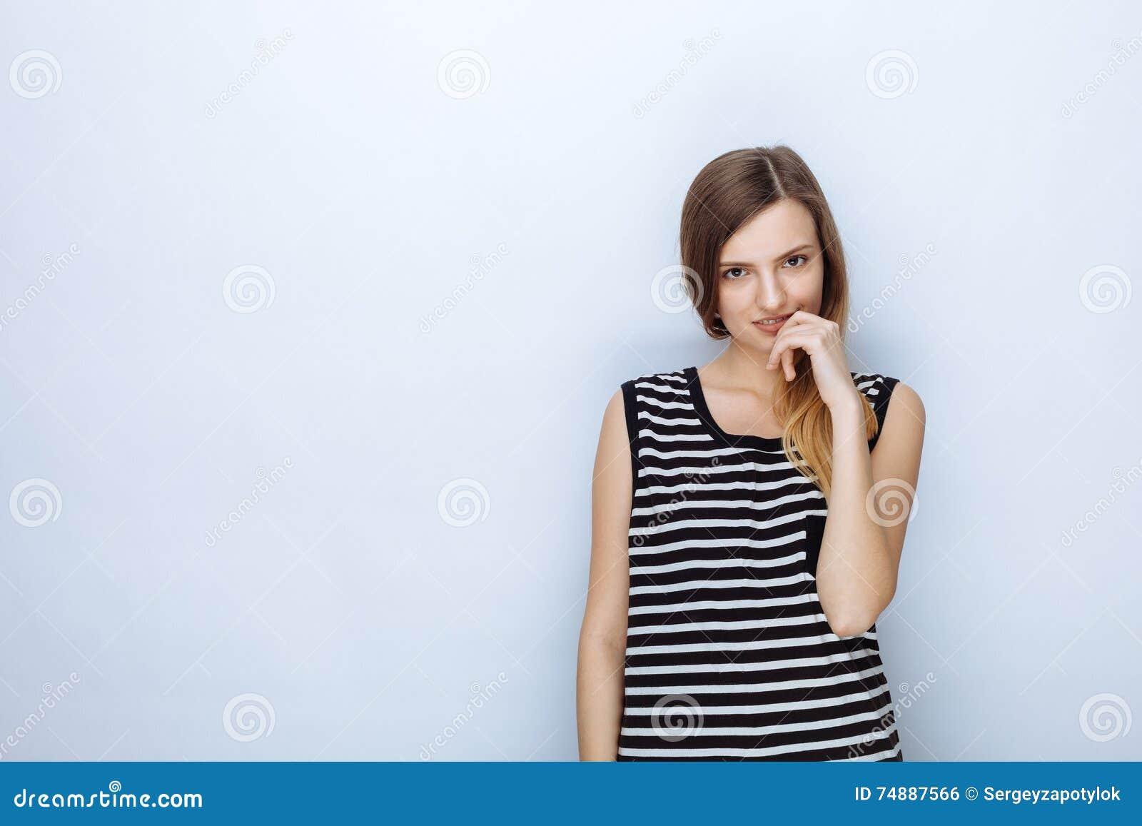 Retrato da mulher bonita nova feliz em camisa listrada que levanta para os testes modelo contra o fundo branco do estúdio
