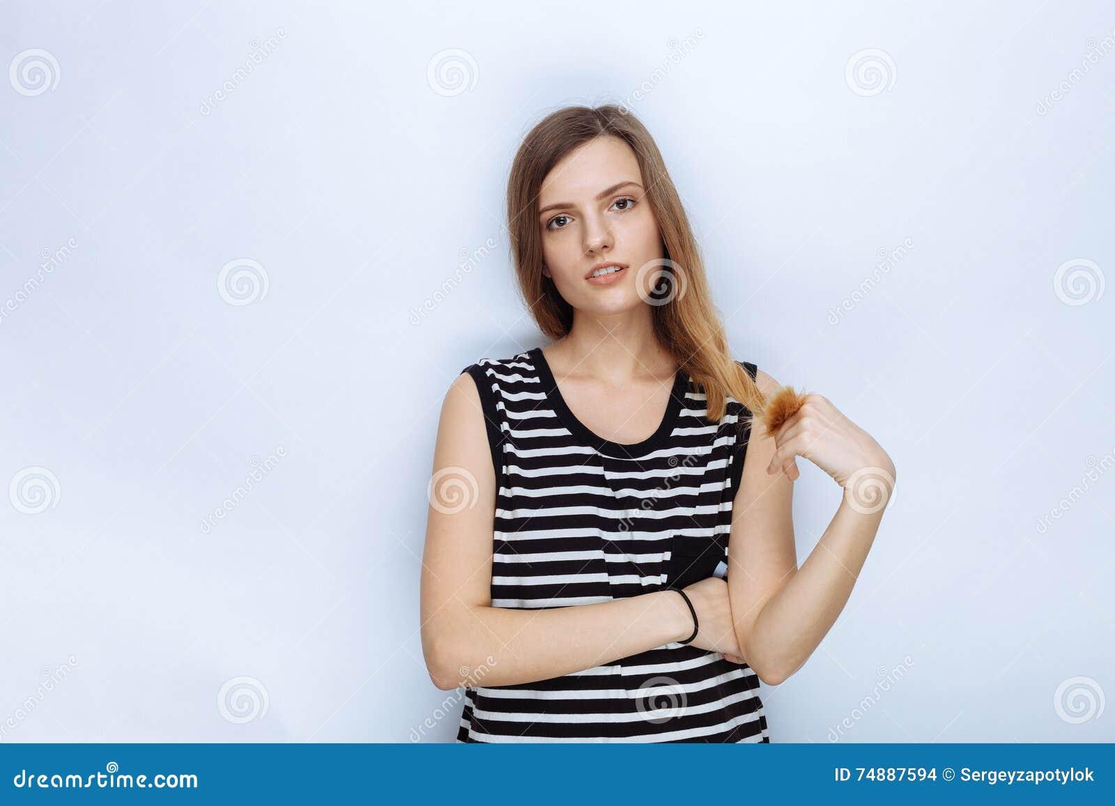 Retrato da mulher bonita nova feliz em camisa listrada que toca em seu cabelo que levanta para os testes modelo contra o fundo br