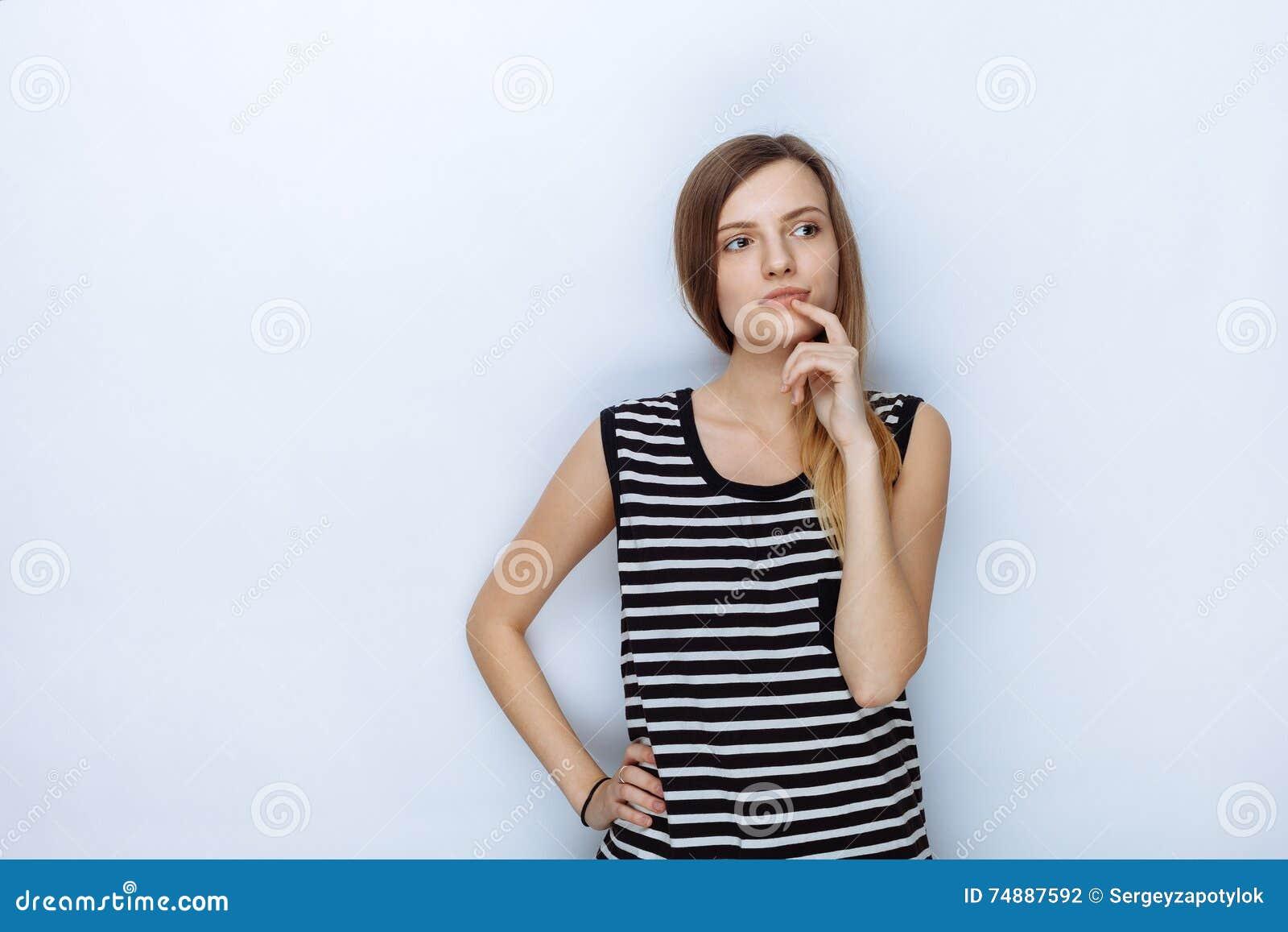 Retrato da mulher bonita nova feliz em camisa listrada que toca em seus bordos que levantam para os testes modelo contra o fundo