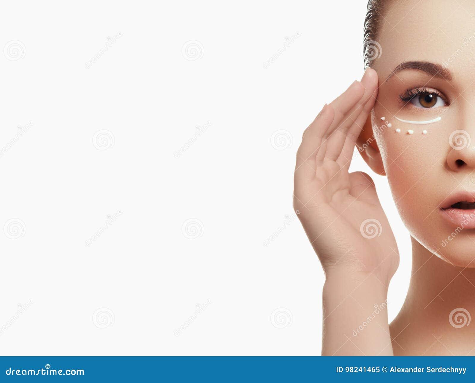Retrato da mulher bonita que aplica algum creme a sua cara para cuidados com a pele