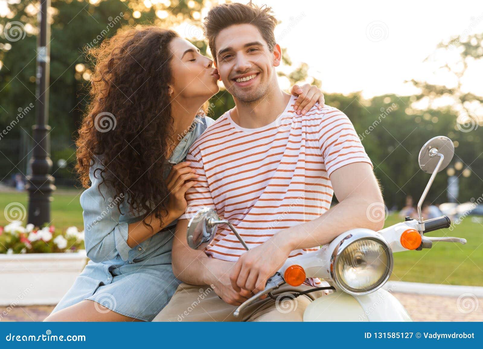 Retrato da mulher bonita que beija o homem caucasiano no mordente ao sentar-se no velomotor