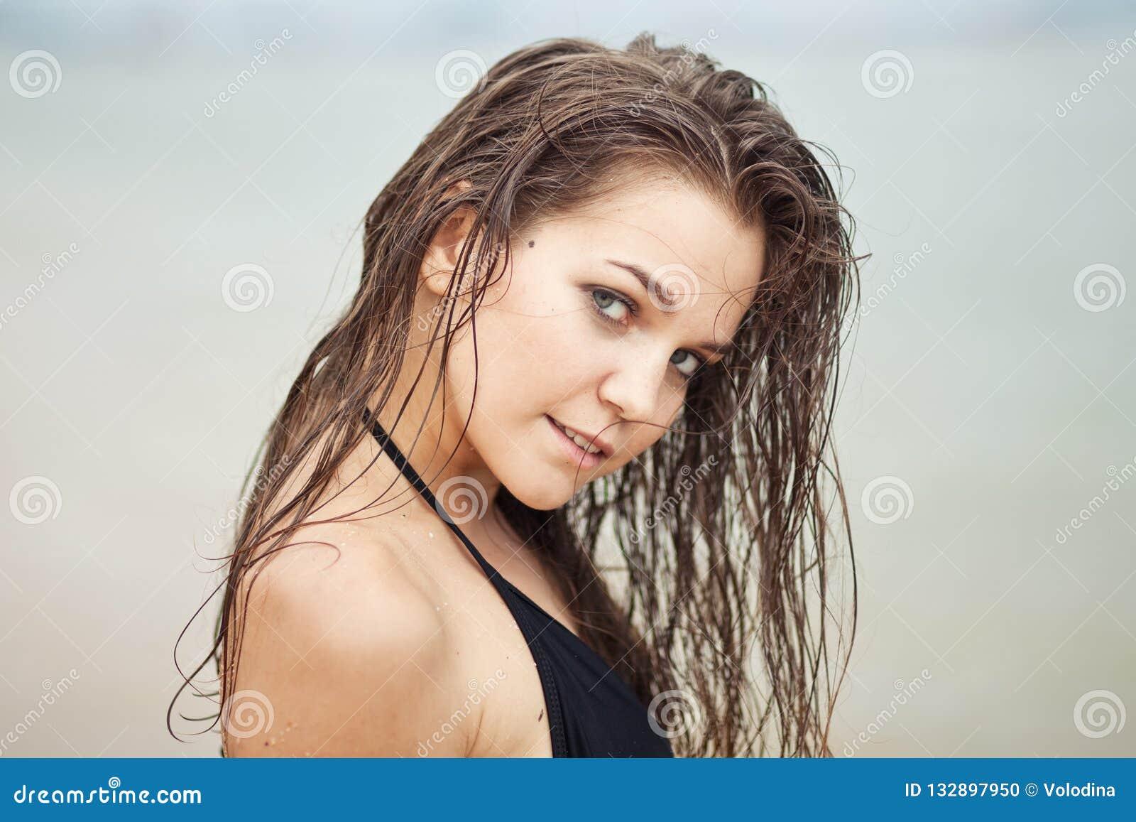 Retrato da mulher com cabelo molhado na praia