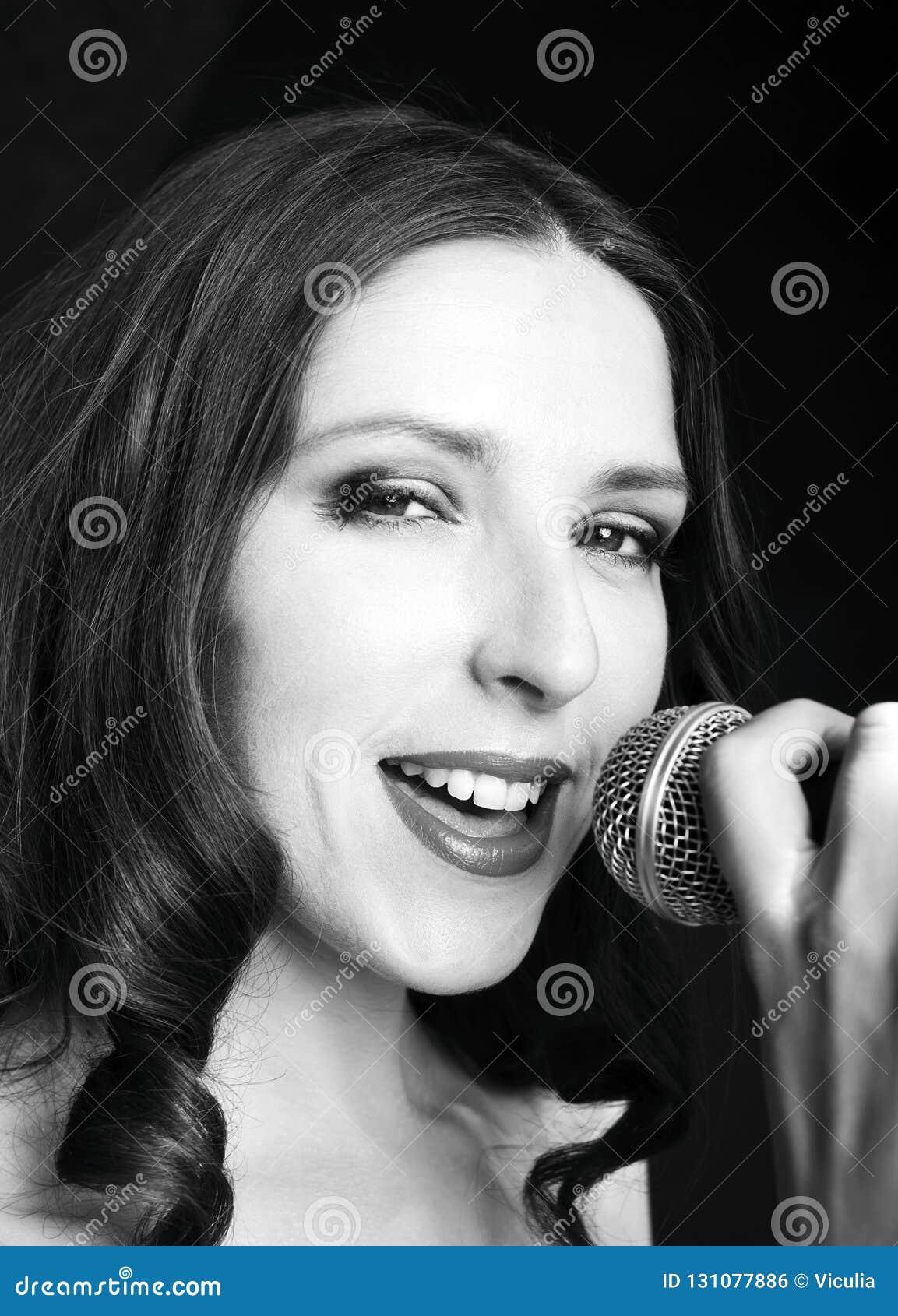 Retrato da mulher de canto bonita no fundo preto, fim acima