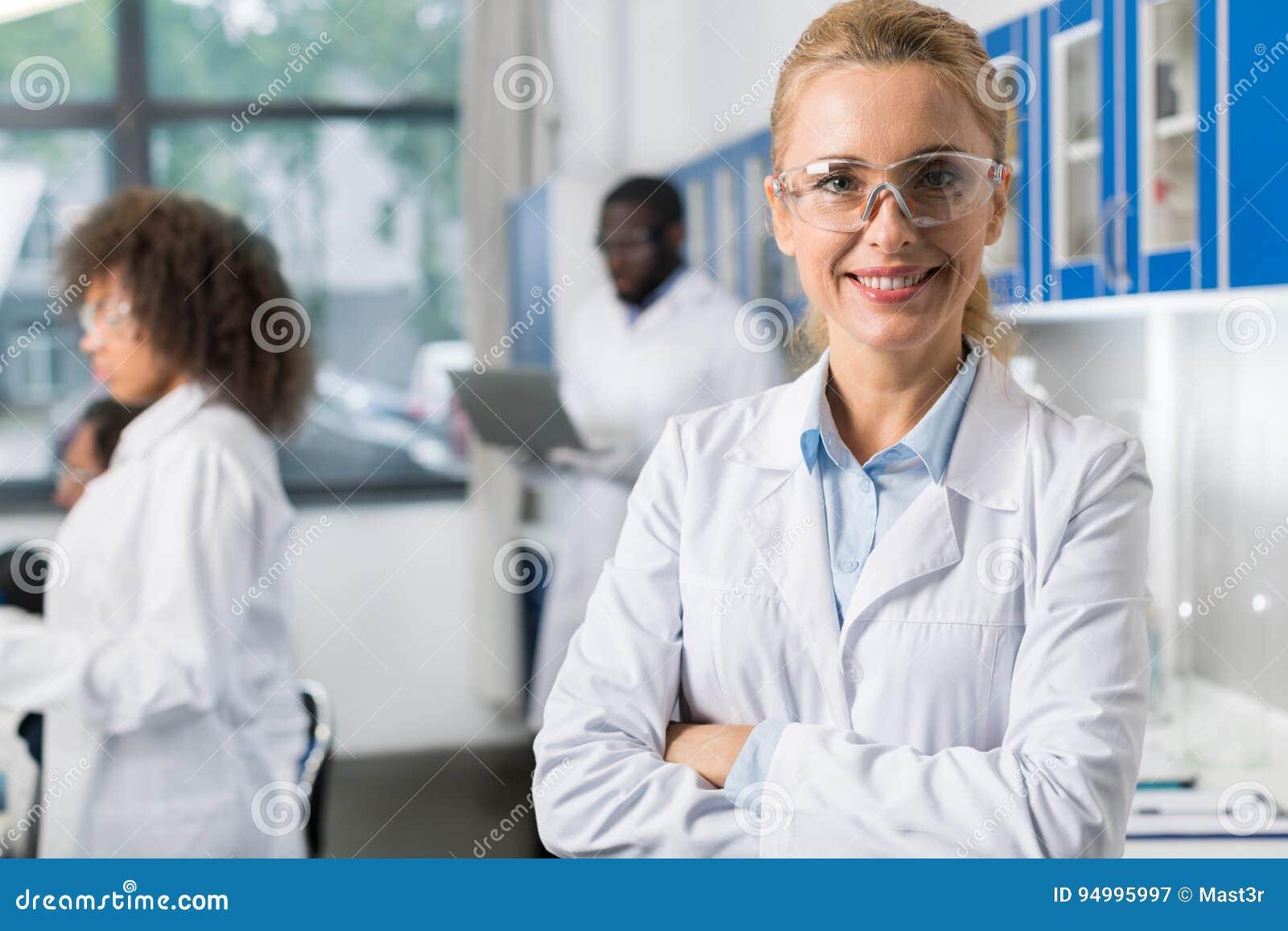 Retrato da mulher de sorriso no revestimento branco e em monóculos protetores no laboratório moderno, cientista fêmea Over Busy