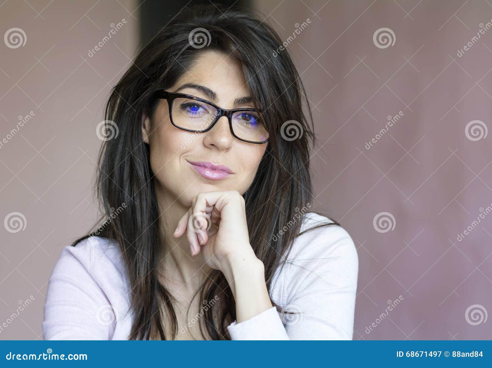Retrato da mulher de sorriso nova bonita com monóculos modernos