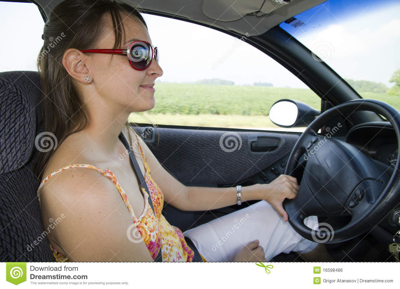 Retrato da mulher de sorriso nova que conduz o carro
