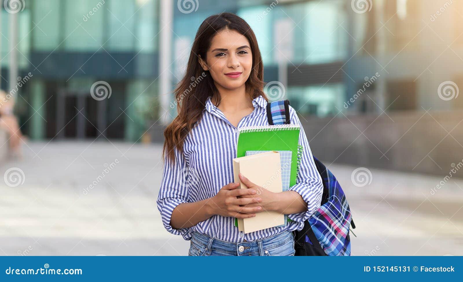 Retrato da mulher de sorriso nova que guarda livros, estudo, educação, conhecimento, conceito do objetivo