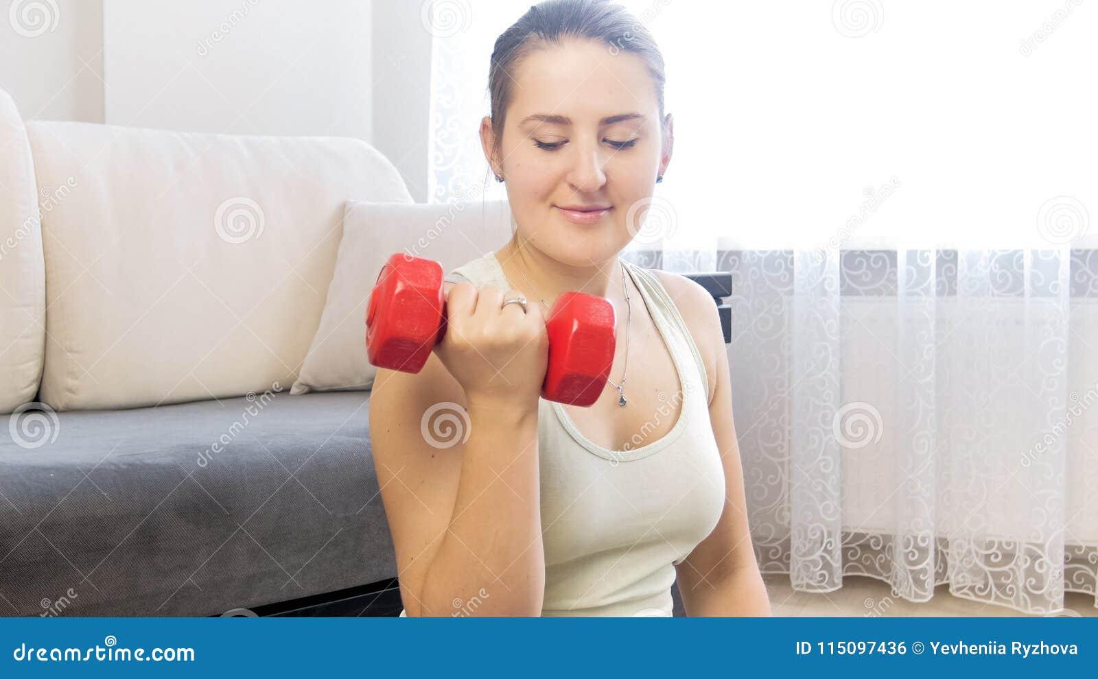 Retrato da mulher desportiva nova que guarda pesos vermelhos