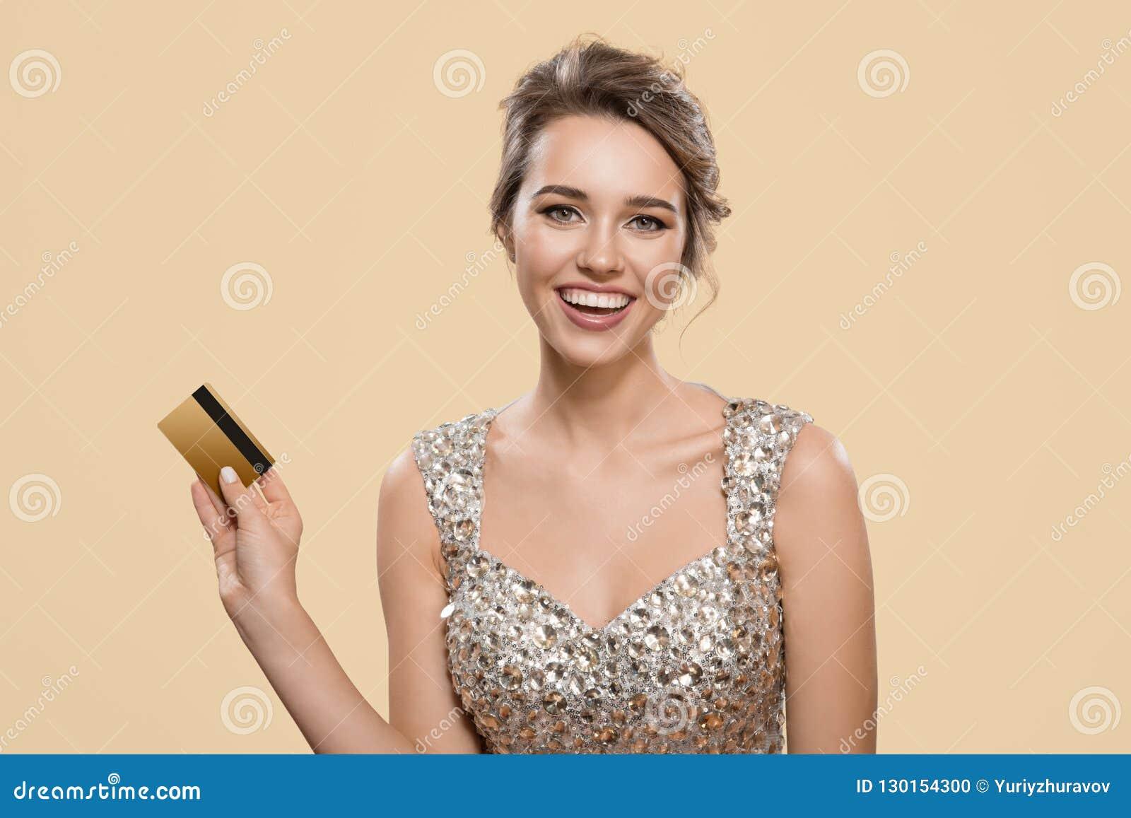 Retrato da mulher encantador feliz que guarda o cartão de banco plástico do ouro