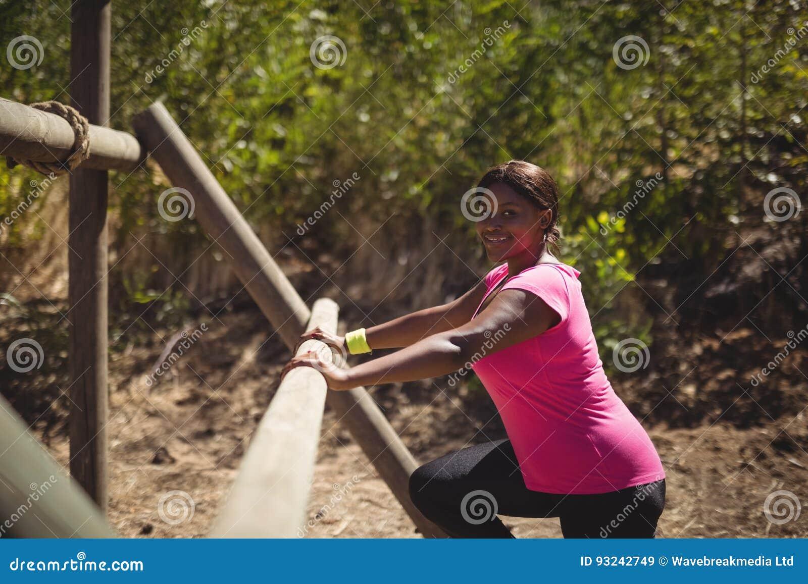Retrato da mulher feliz que exercita no equipamento exterior durante o curso de obstáculo