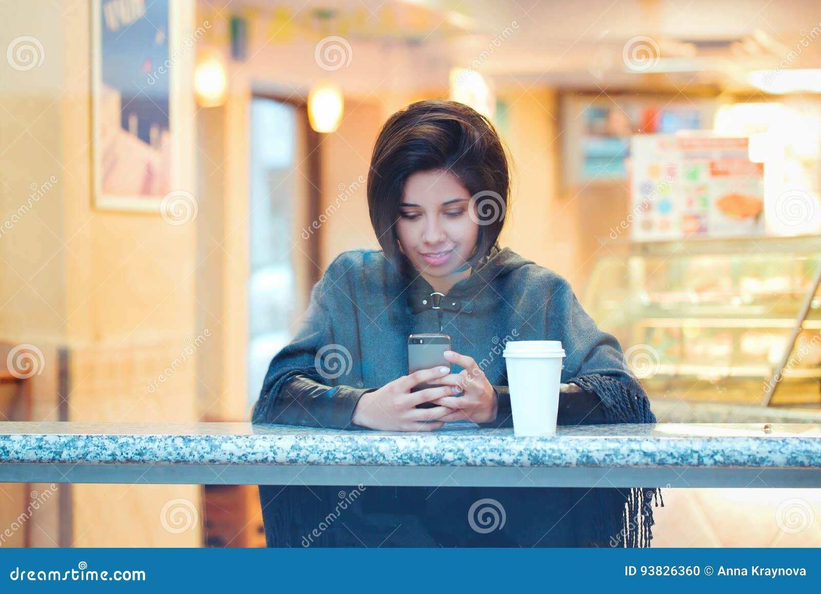 Retrato da mulher latino-americano latin da menina do moderno novo bonito com o prumo do cabelo curto no revestimento cinzento do