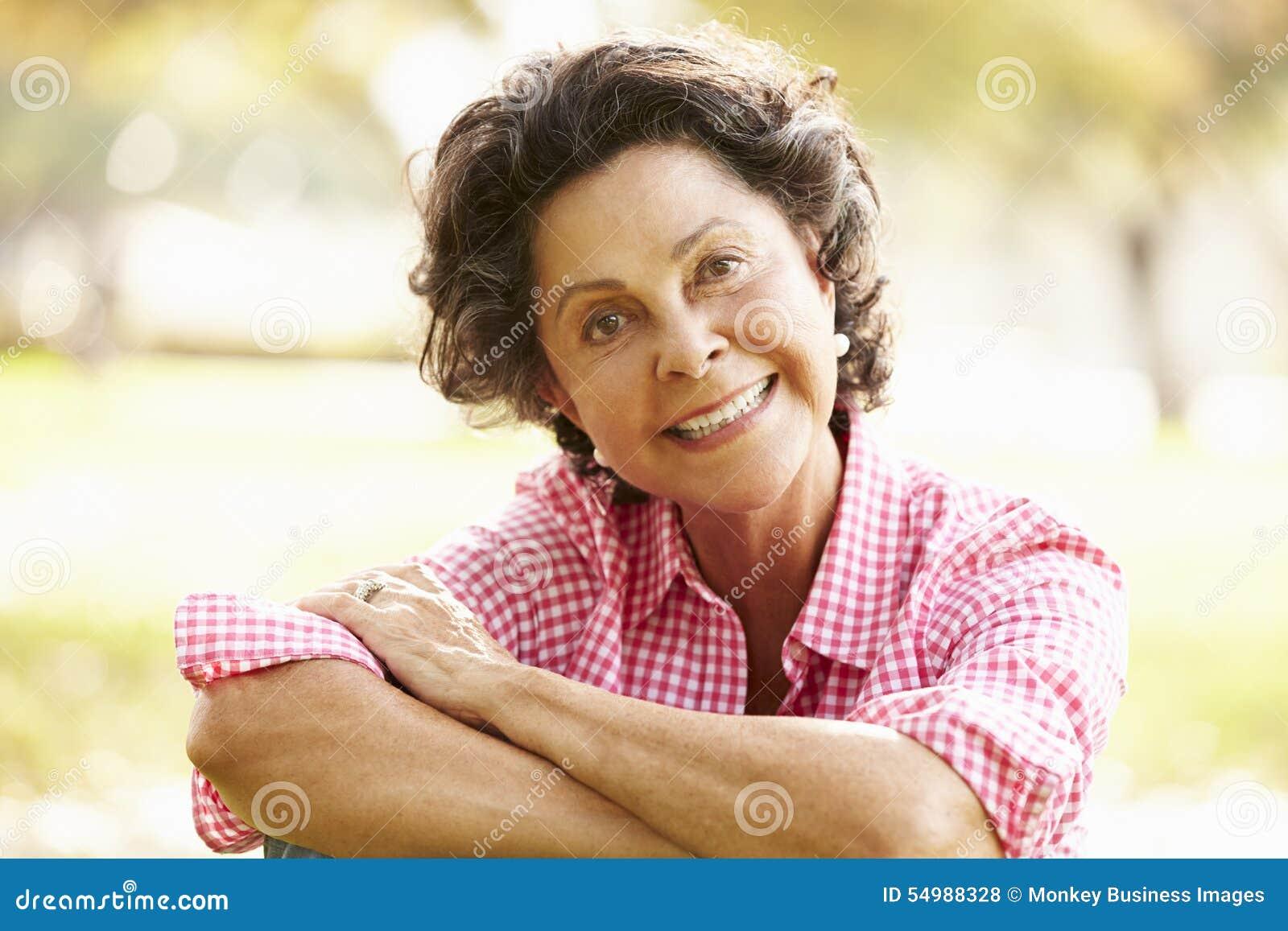 Retrato da mulher latino-americano superior que senta-se no parque