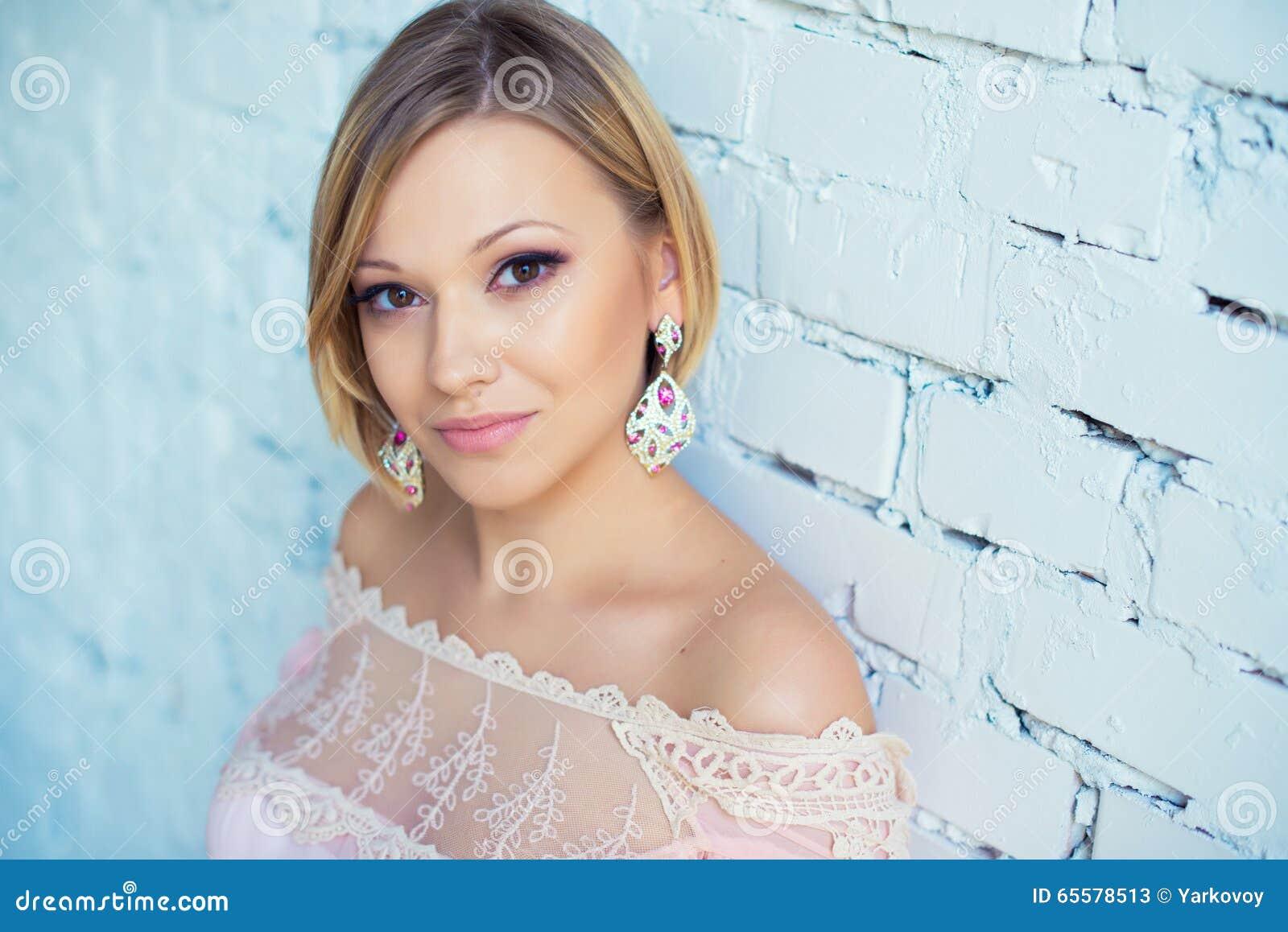 Retrato da mulher loura consideravelmente nova com cabelo curto em um fundo da parede de tijolo branca