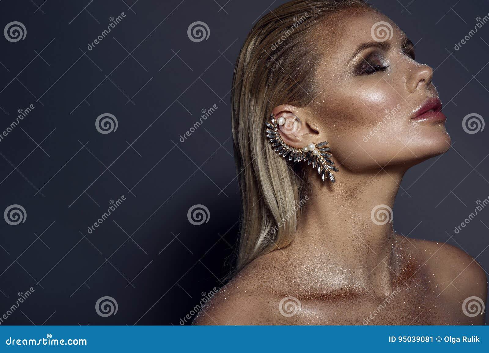 Retrato da mulher loura lindo chique com cabelo molhado, composição de brilho artística e o punho em sua orelha